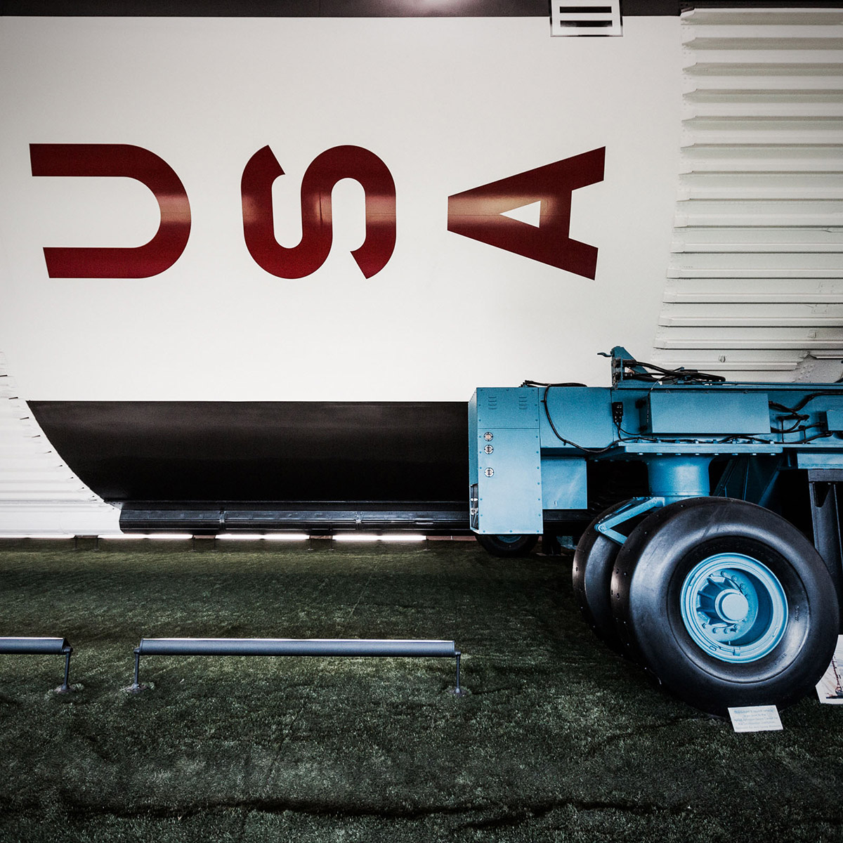 Side of large rocket on horizontal carrier with USA symbol on it by Jordan Reeder