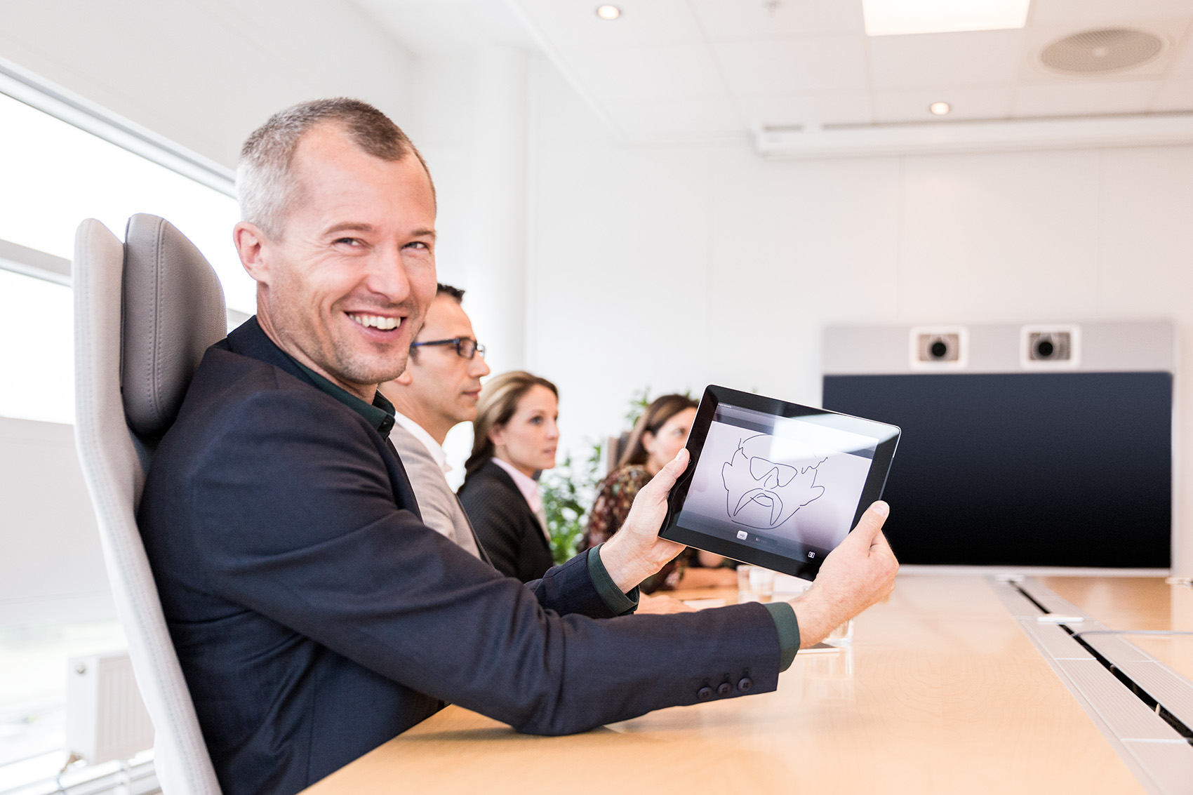 Man smiles with a tablet during modern boardroom conference meeting with team