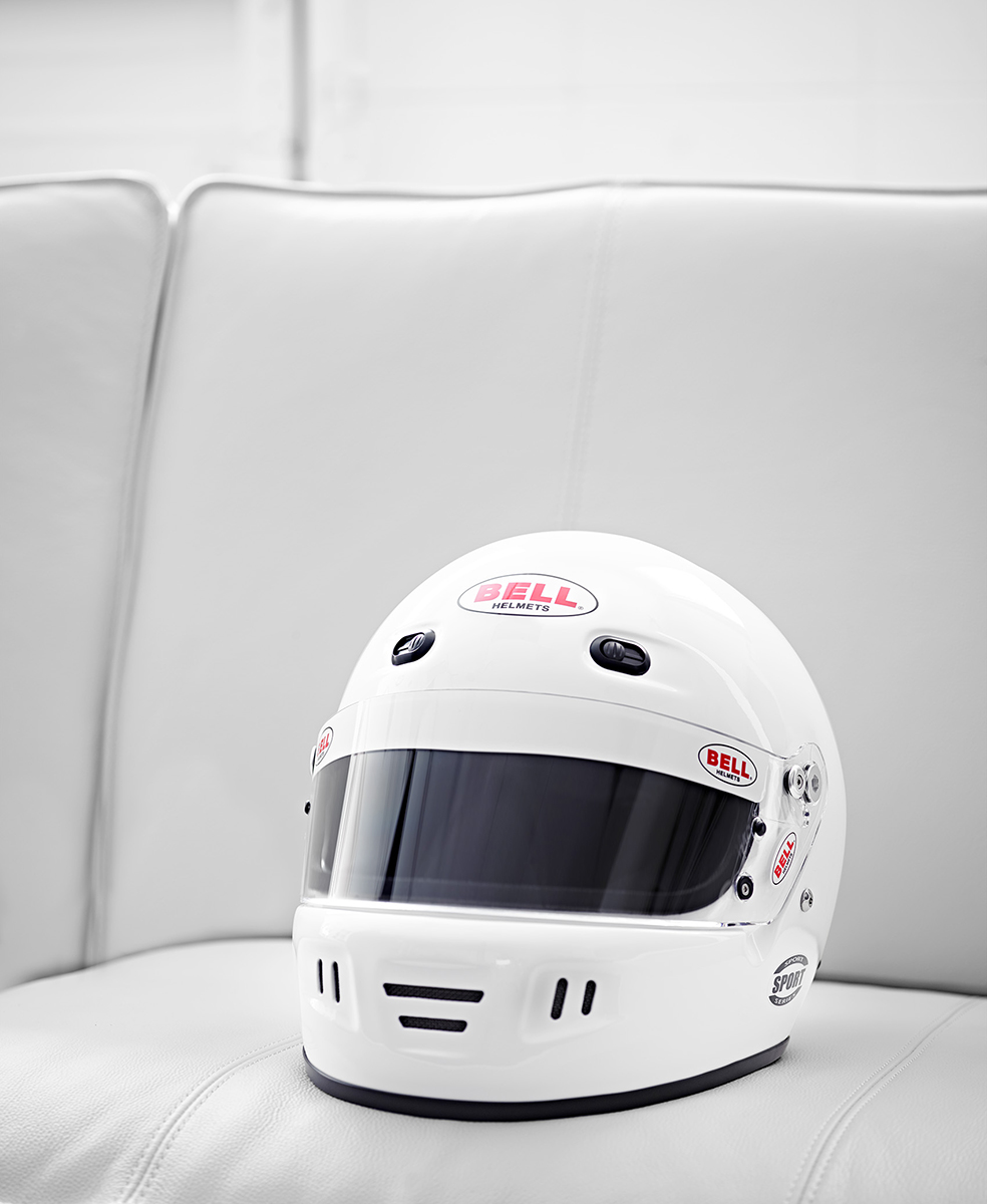 beautiful still life of Bell motorsports motorcycle Racing Helmet on a white couch