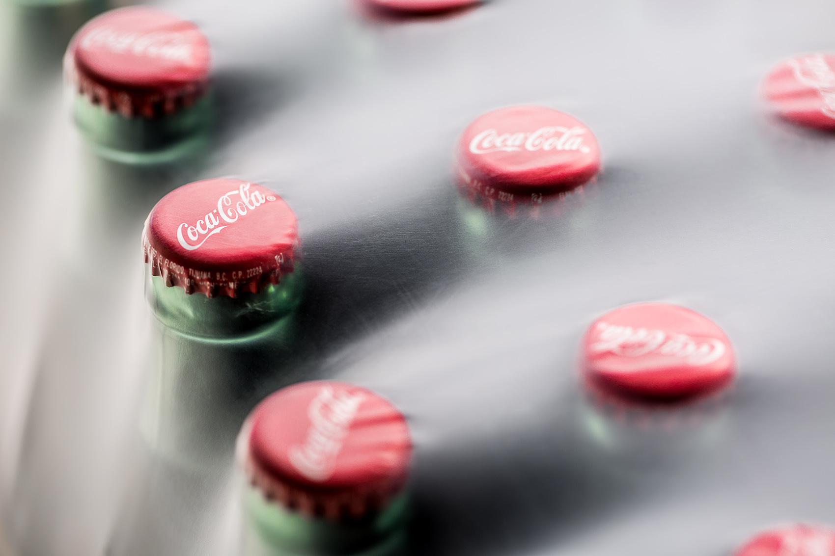 Coca Cola soda bottles close up under plastic wrap packaging