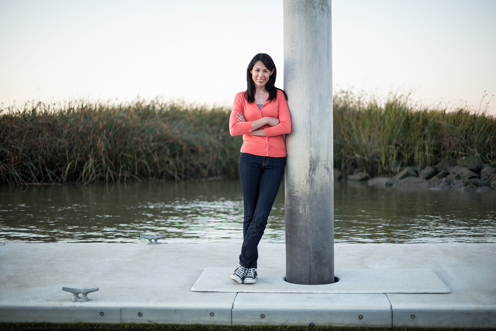 cute latino woman portrait outside leaning against a post by lake