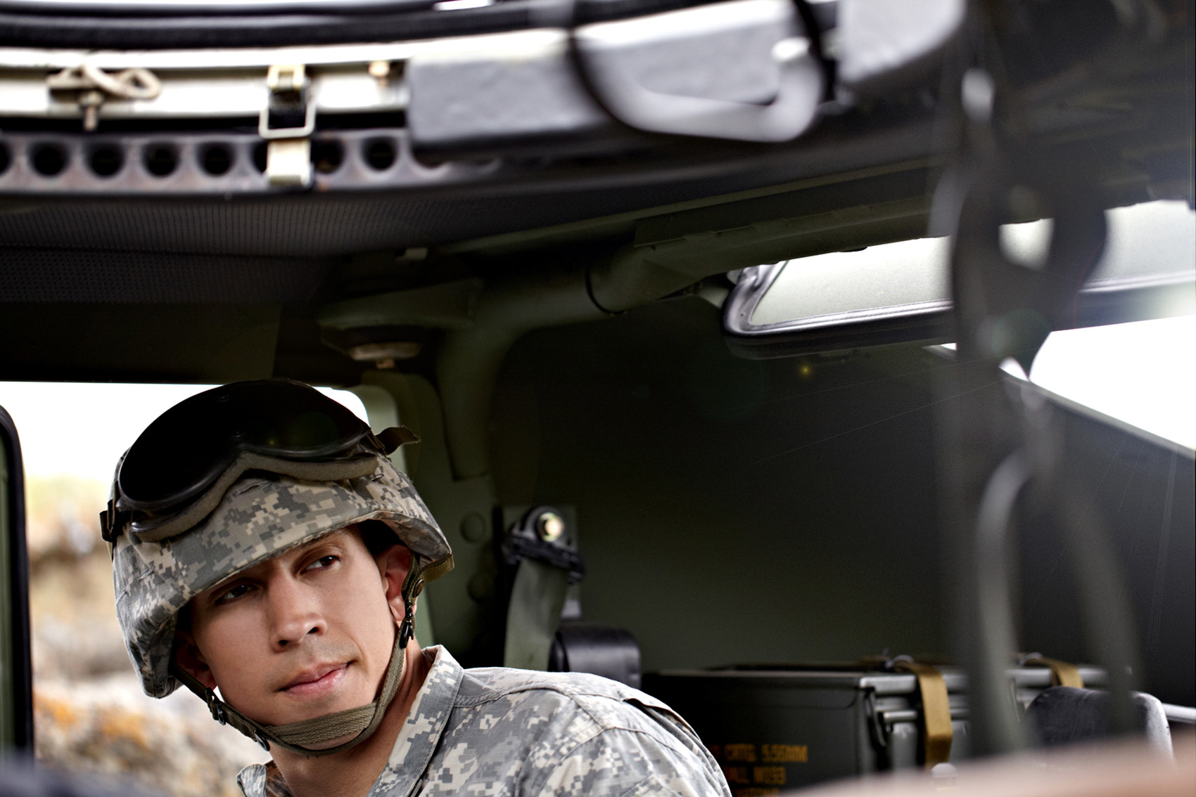 hispanic male soldier lifestyle inside of a hummer or humvee