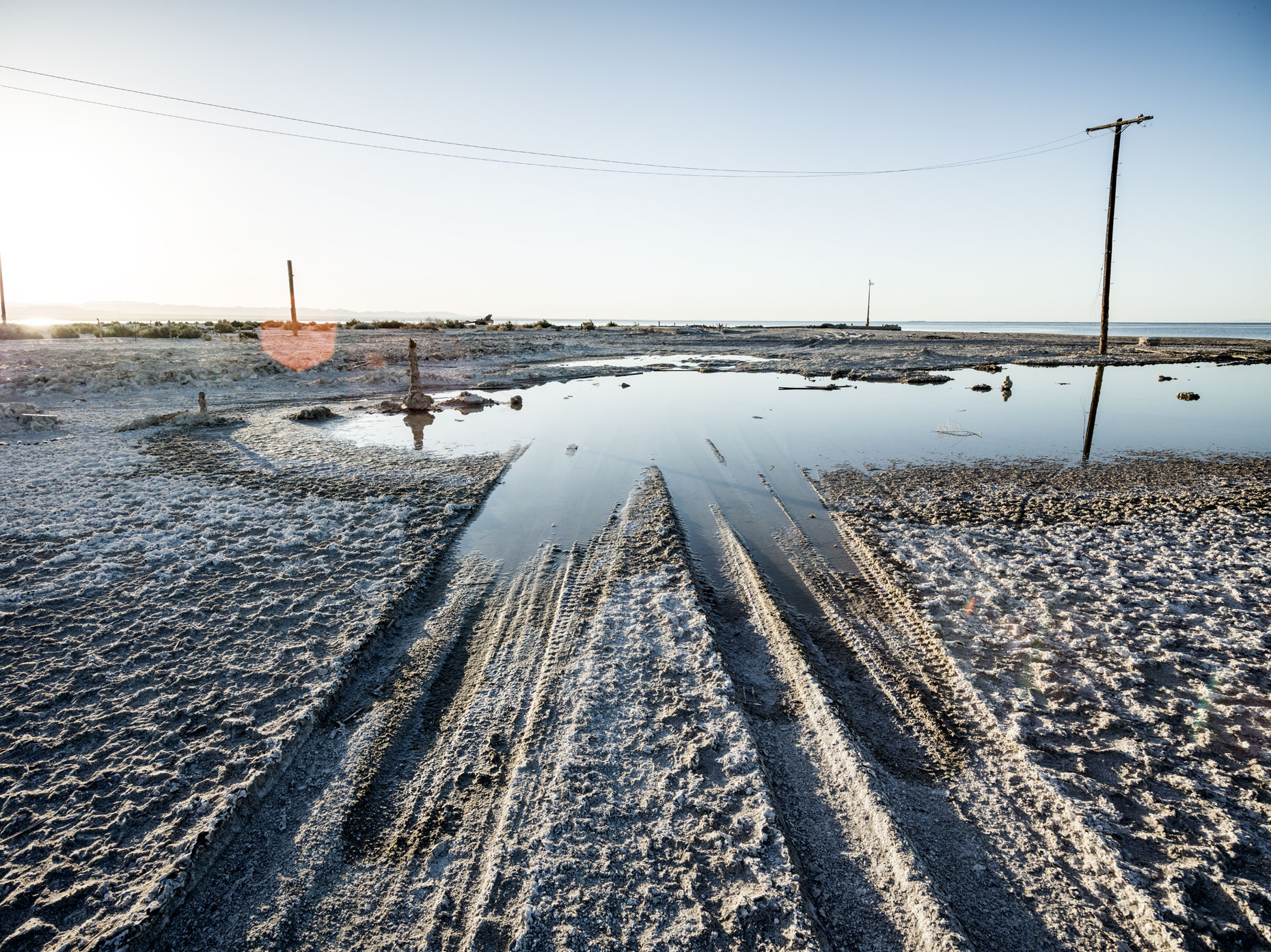 Bombay Beach puddle of water with tire tracks in the sand leading into the Salton Sea