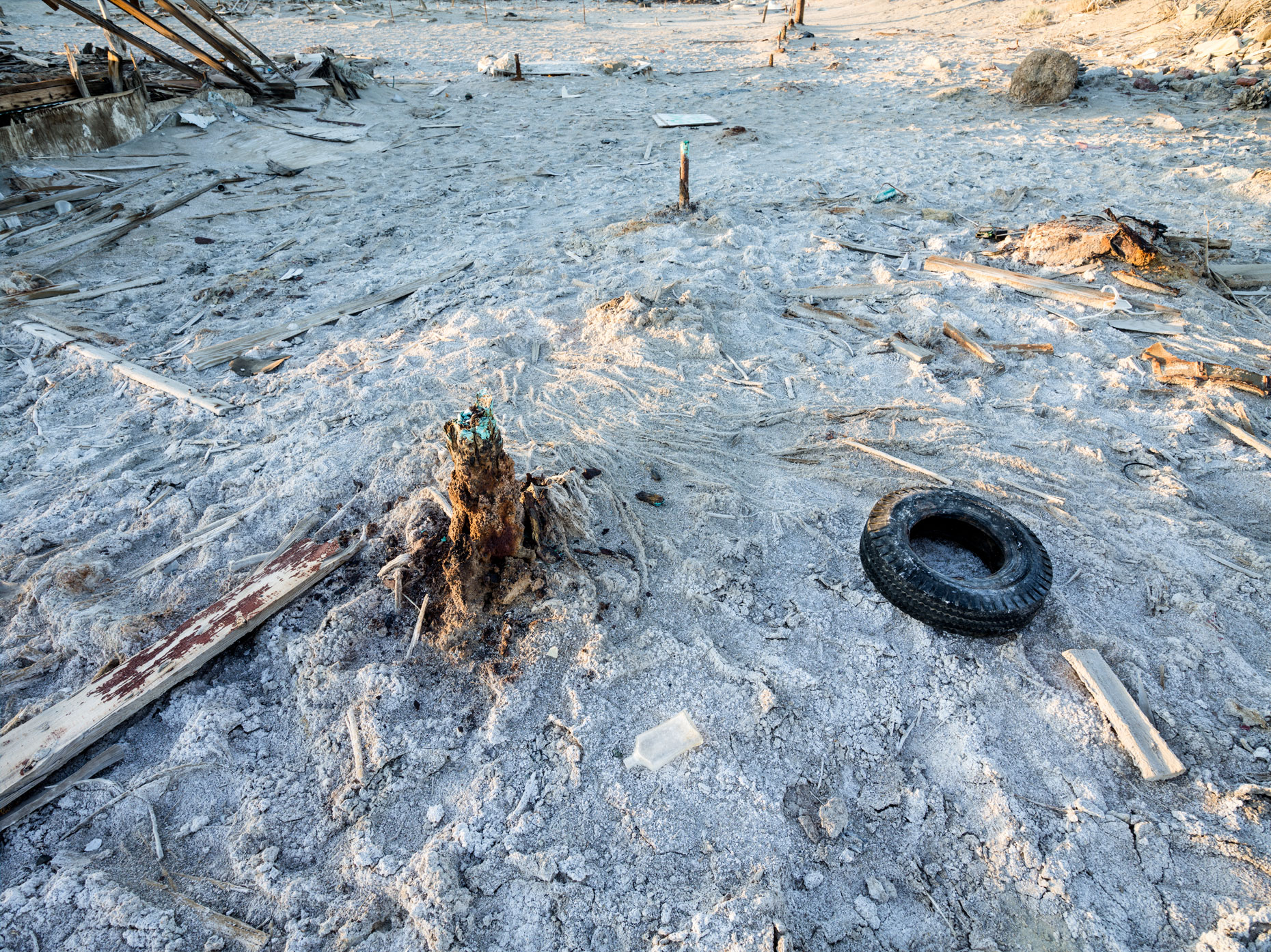 Salton Sea sand castle with tires and other garbage on the Bombay Beach shoreline