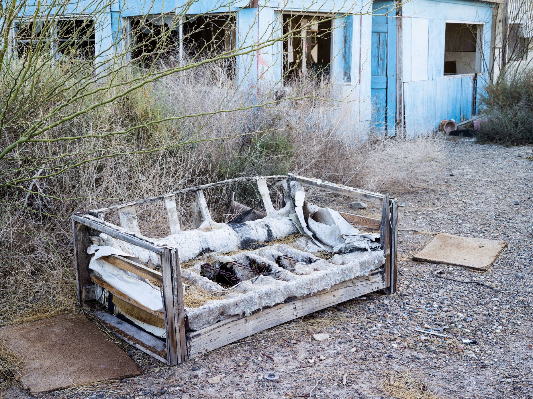 Bombay Beach weathered couch outside of an abandoned building