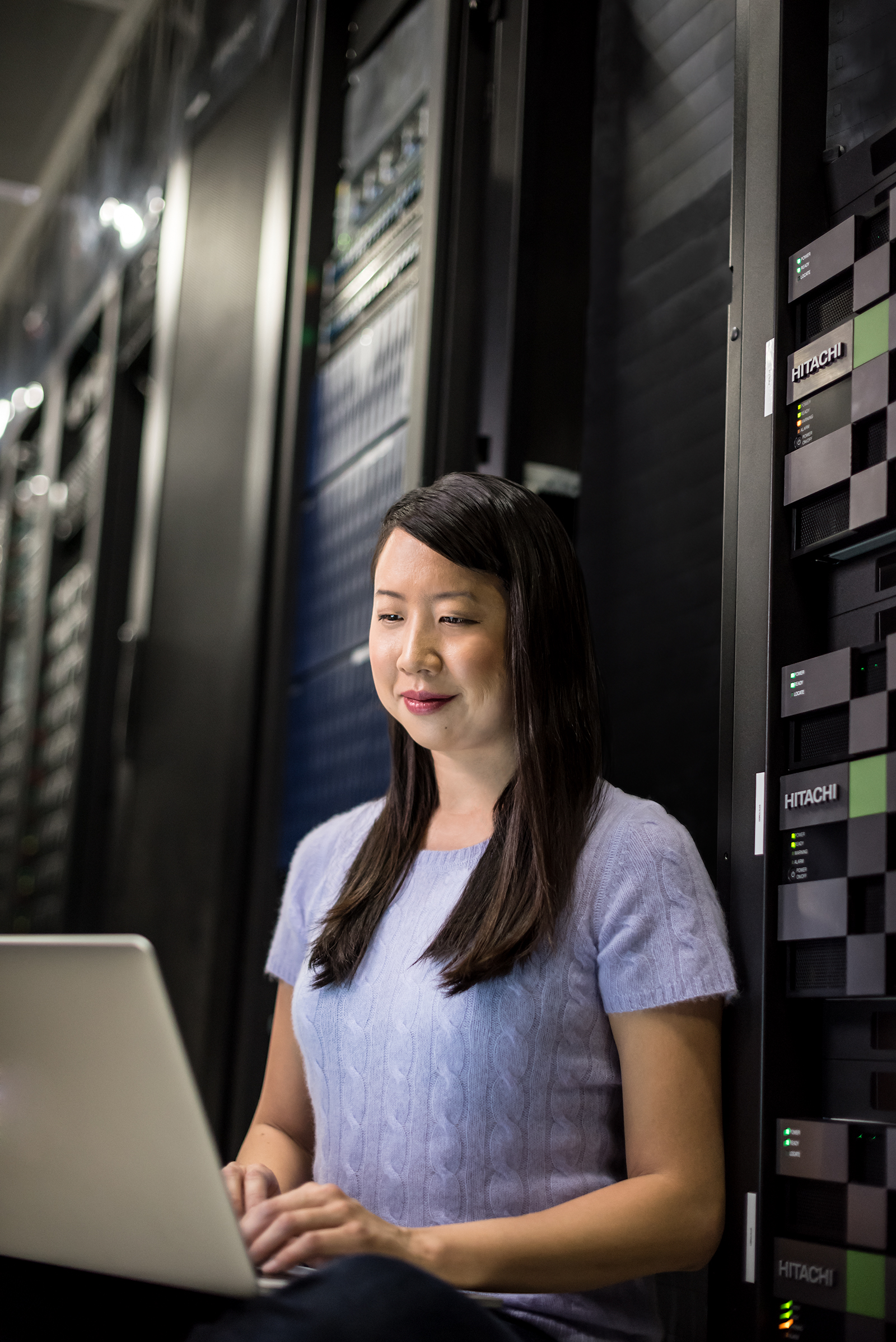 Young asian woman on a laptop in a data center
