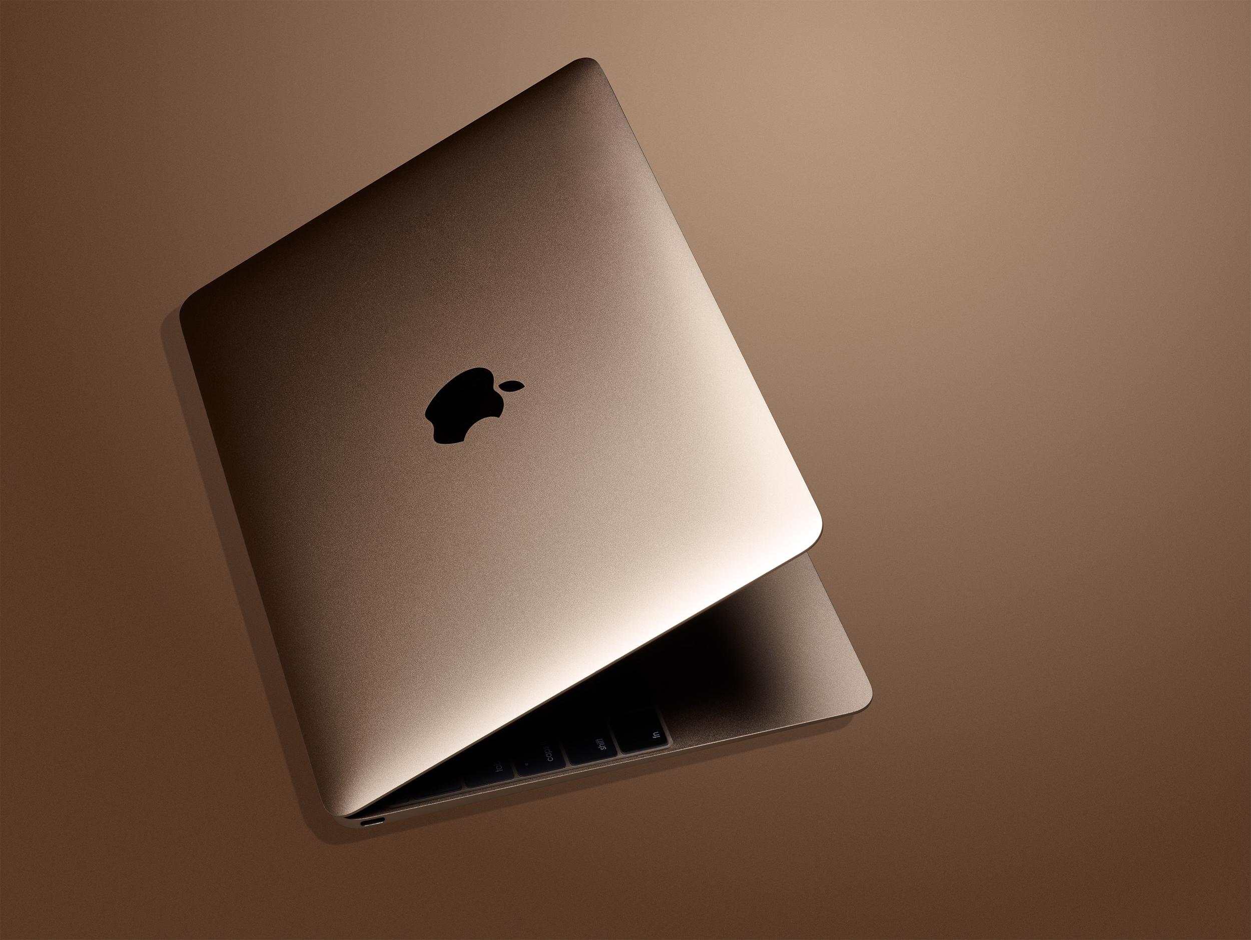 Gold Apple laptop computer on golden background