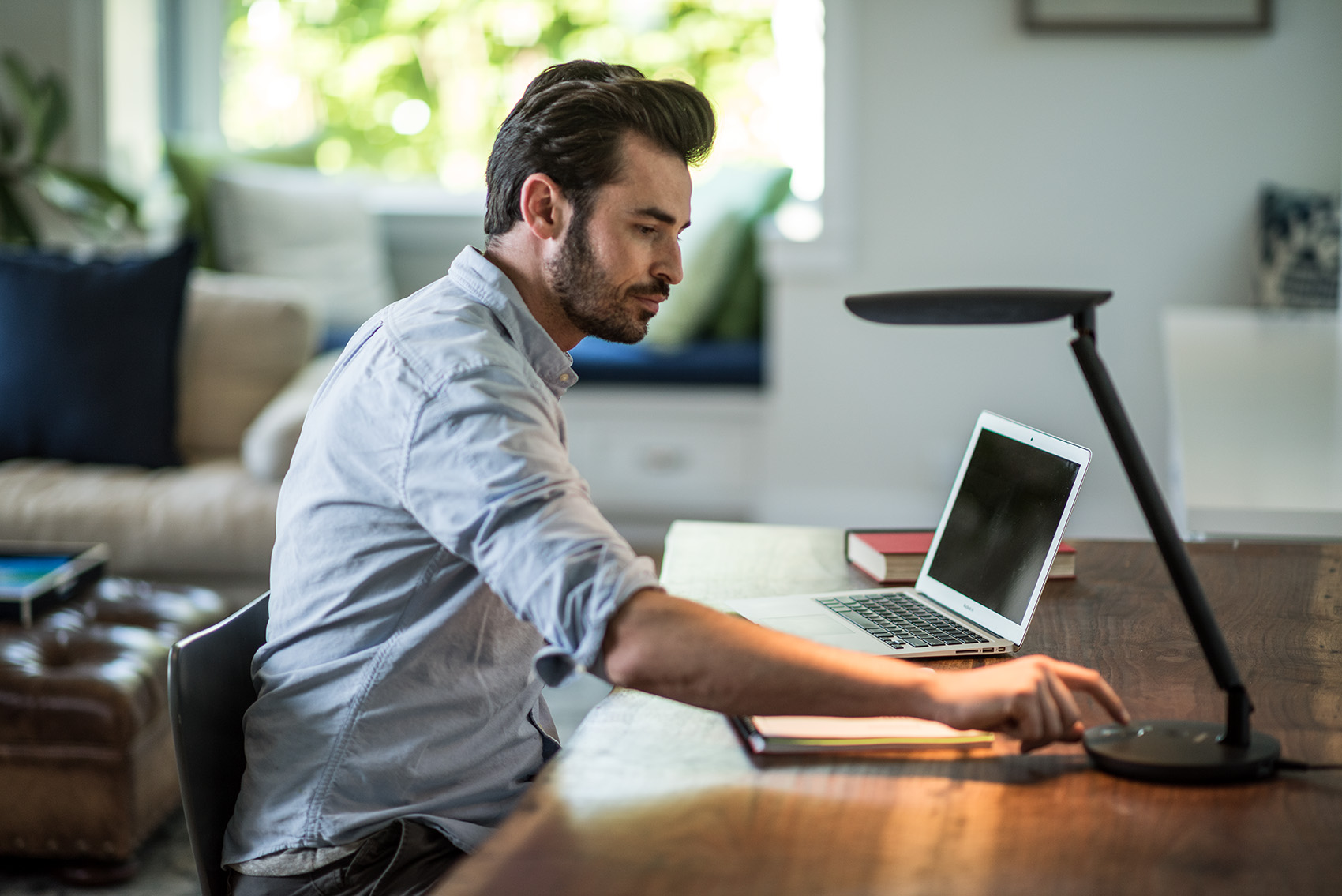 Man turning on a light while working at home