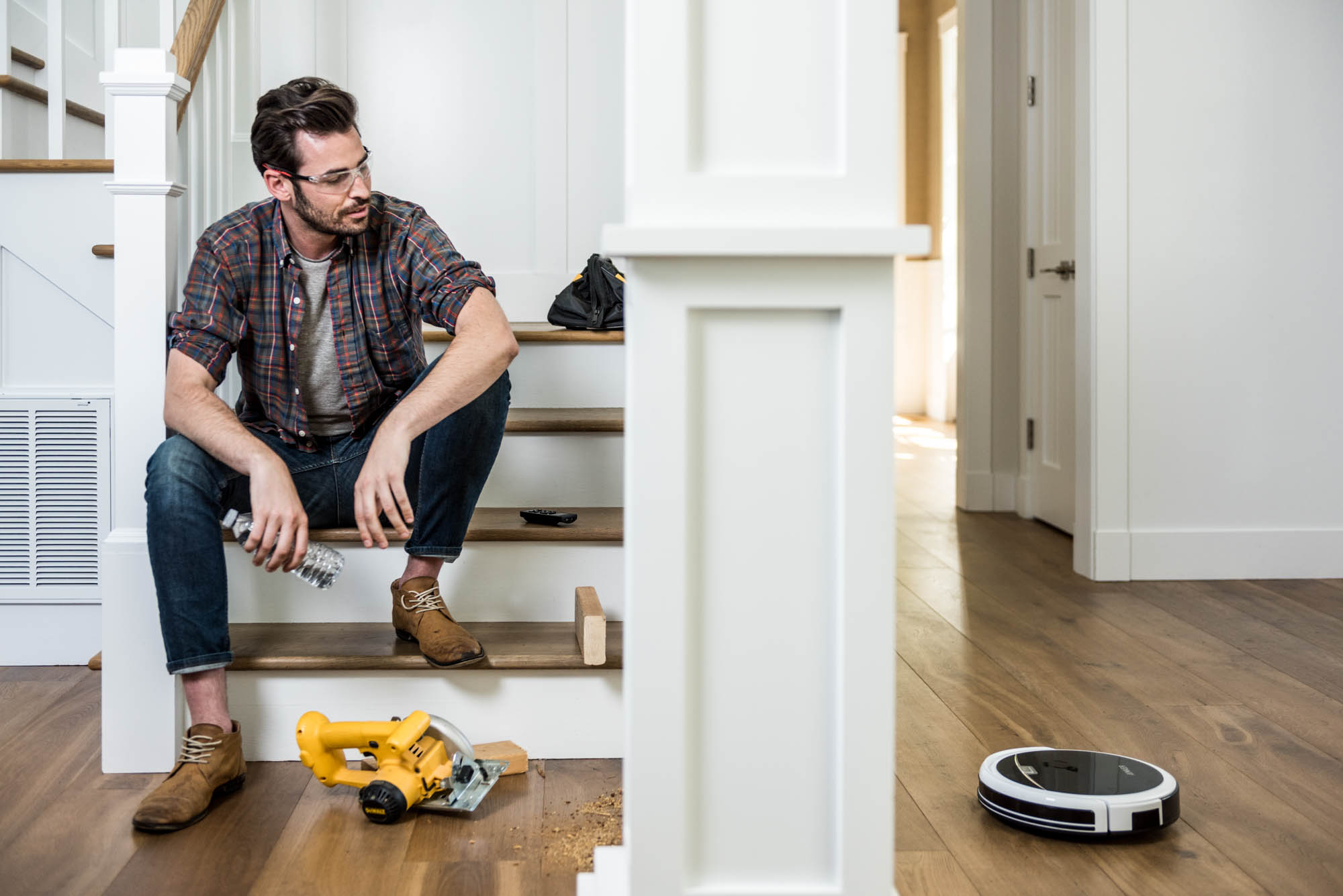 Man sitting on stairs with tools and a vacuum