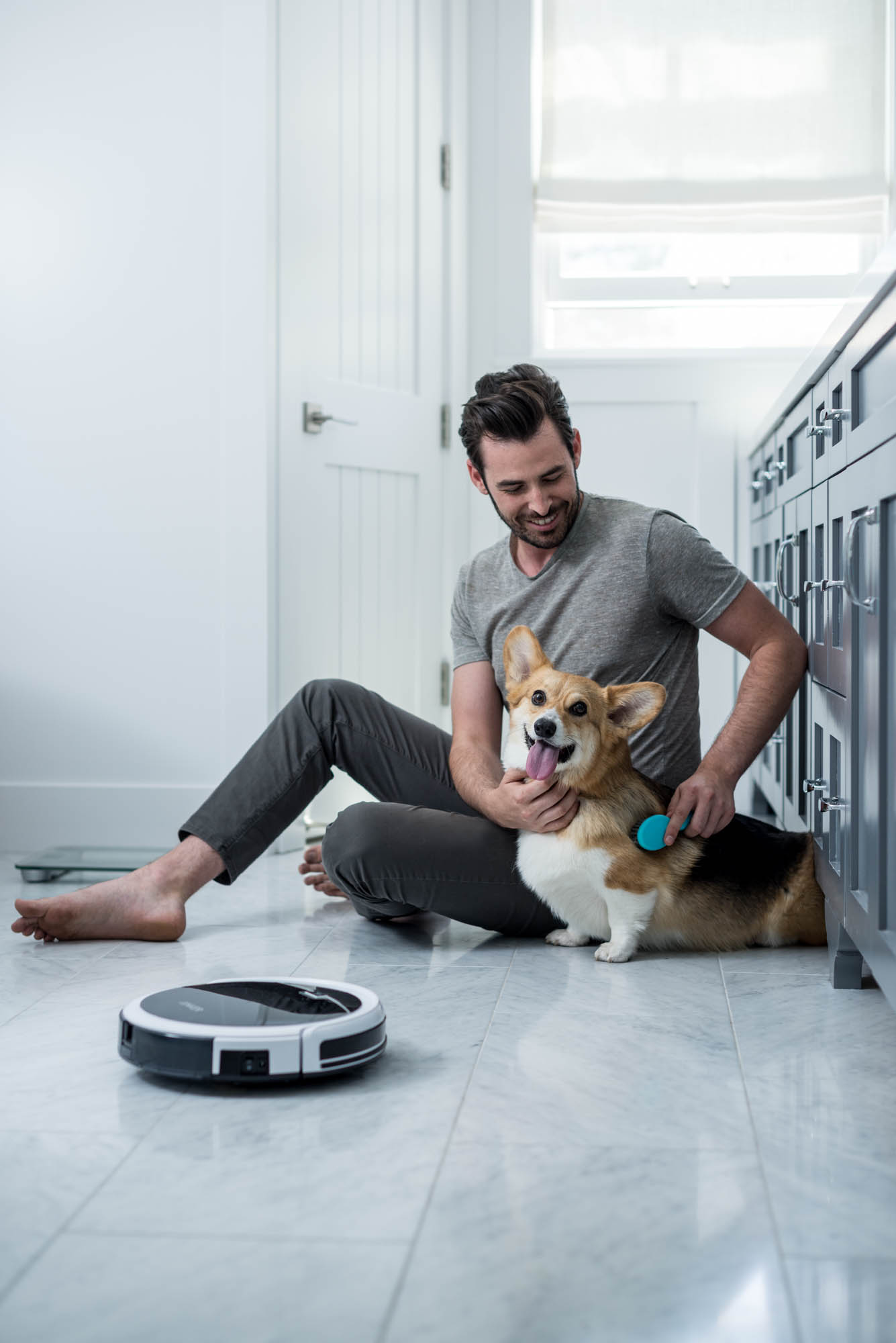 Man with Corgi dog and vacuum