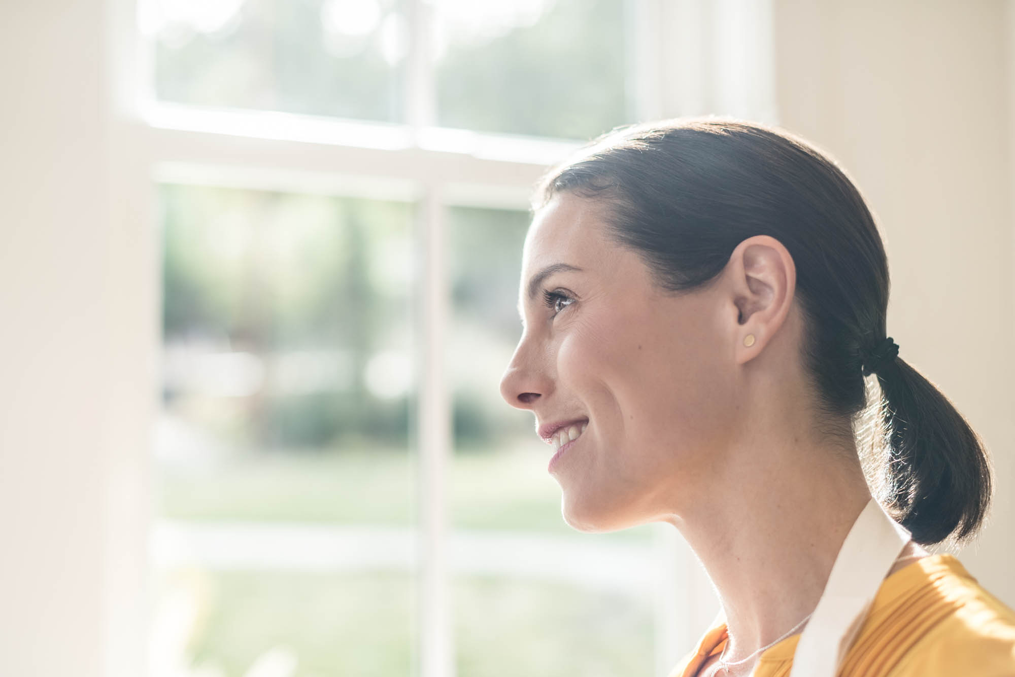 Young woman smiling and looking out of a kitchen window
