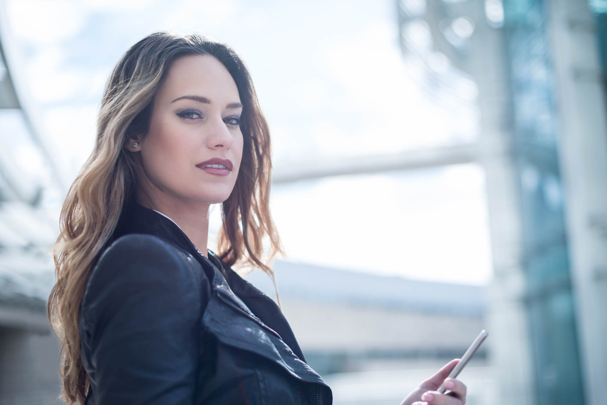 Young woman in leather jacket holding a cellphone