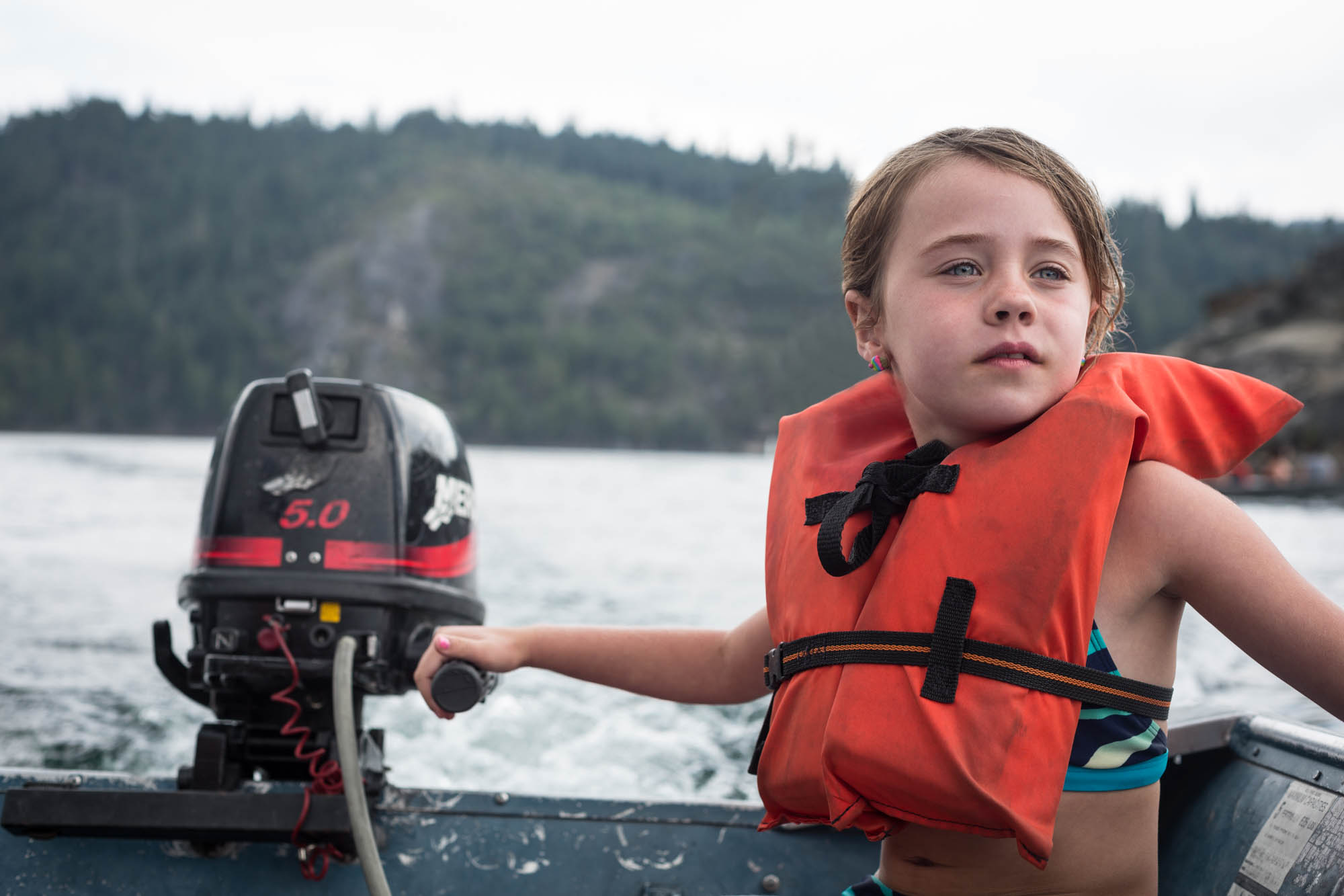 Young girl wearing a life vest steering a boat