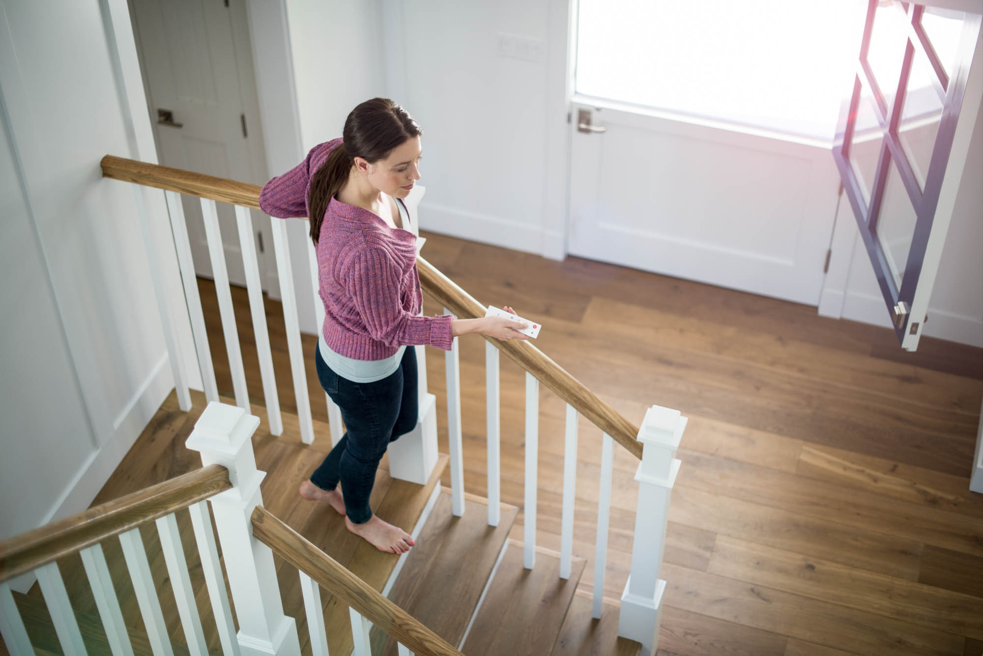 Young woman walking down stairs holding a remote