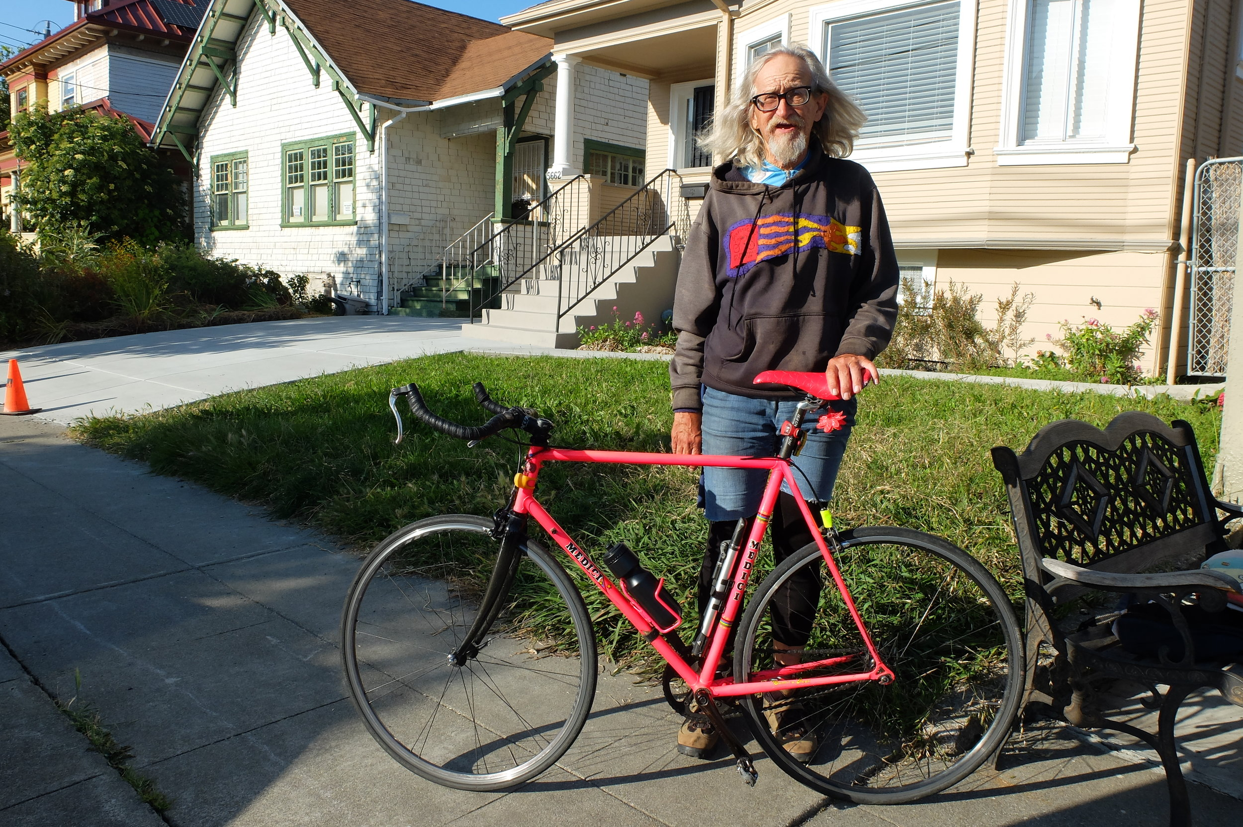 Roger, a retired bike messenger, stands with his pink Medici fixed gear bicycle.