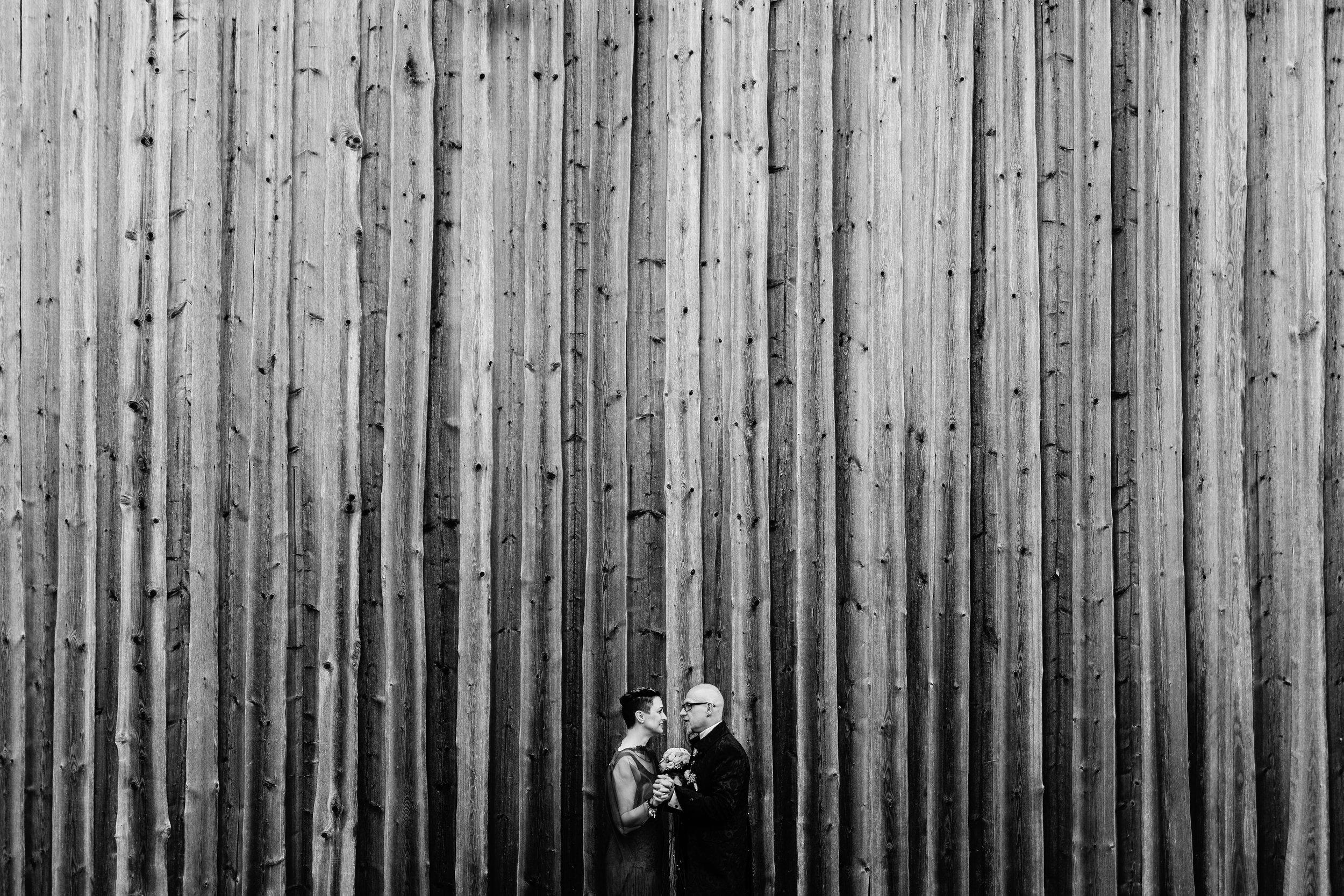 Hochzeitsporträt von Conny und Peter vor einer Holzwand