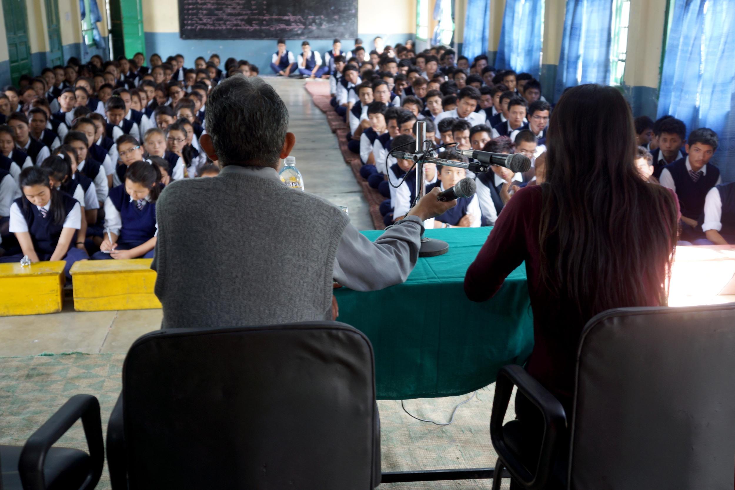 Tibetan students sit in rows as two presenters speak