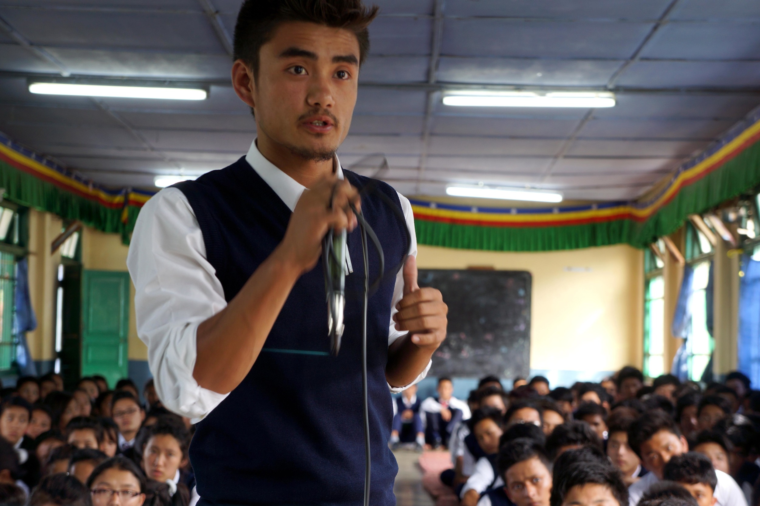 Tibetan student stands with microphone in hand