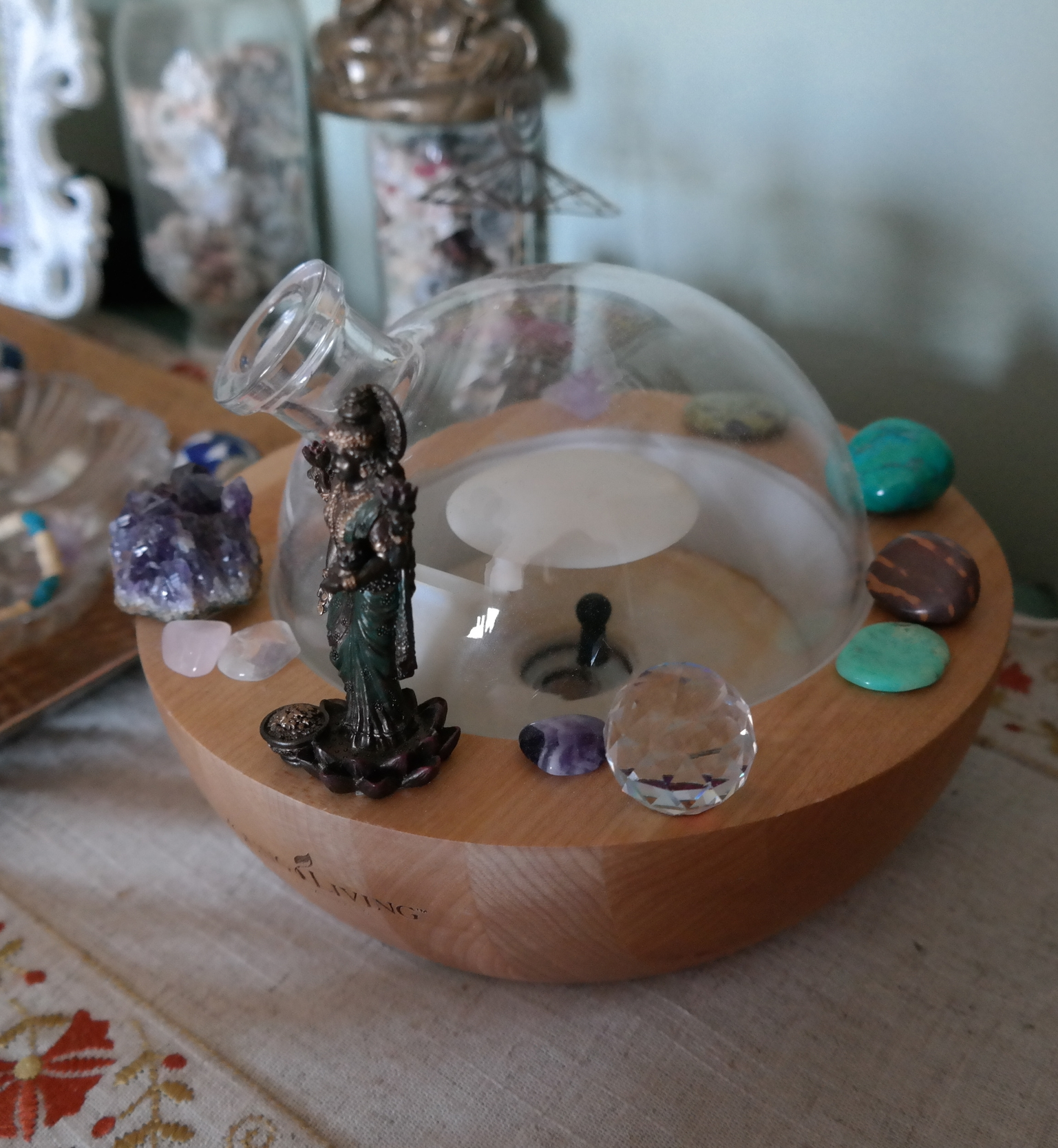 Young Living Oil Diffuser surrounded by crystals and Lakshmi