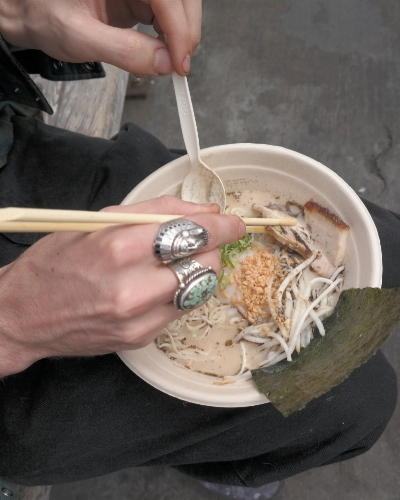 My brother enjoying some hot ramen by the breezy bay