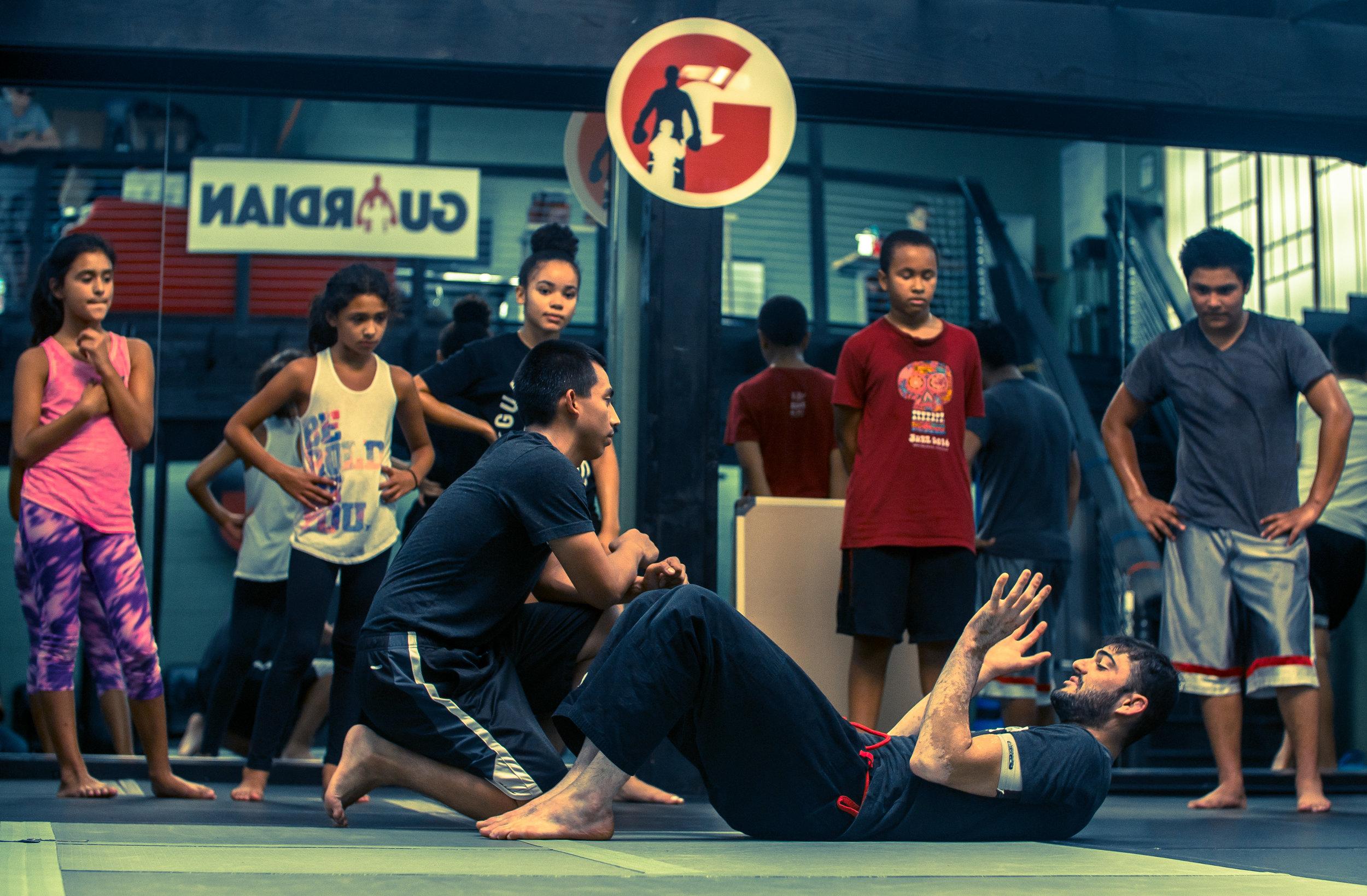 Coach Caleb Khan demonstrating jiu-jitsu techniques