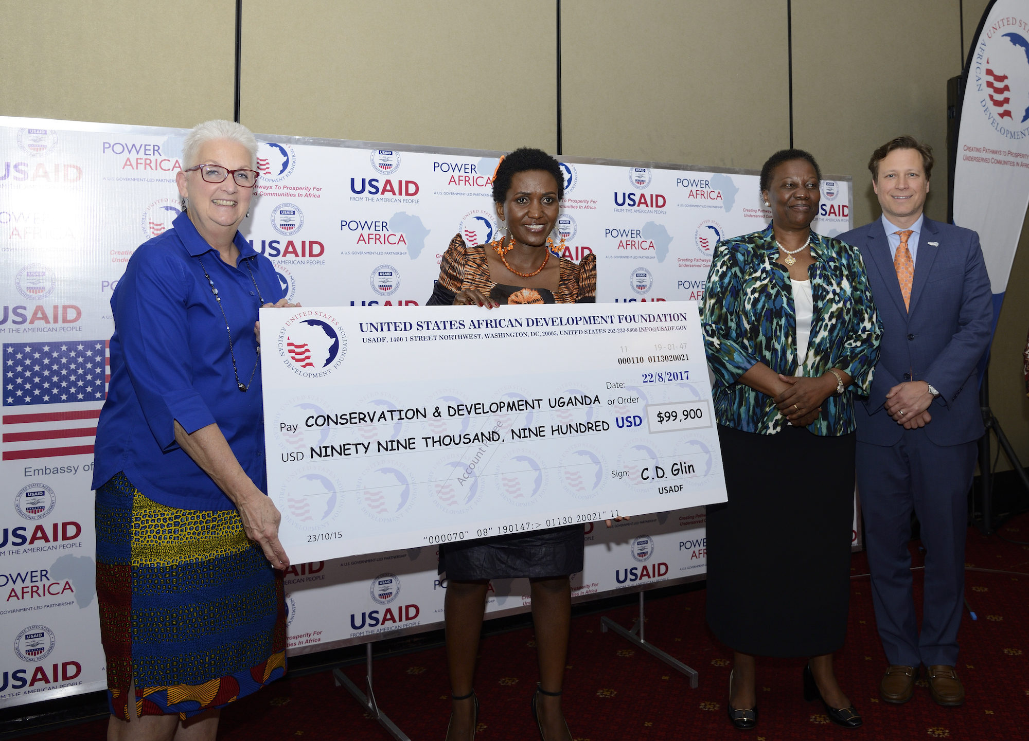 Ambassador Malac, Power Africa Coordinator Andrew Herscowitz   and Hon. Irene Muloni, Minister of Energy and Mineral Development, award   Eseza Musoki,  CEO of CODE Uganda .    USADF, a Power Africa partner, awarded 2 grants to women-owned energy enterprises in Uganda in August 2017.