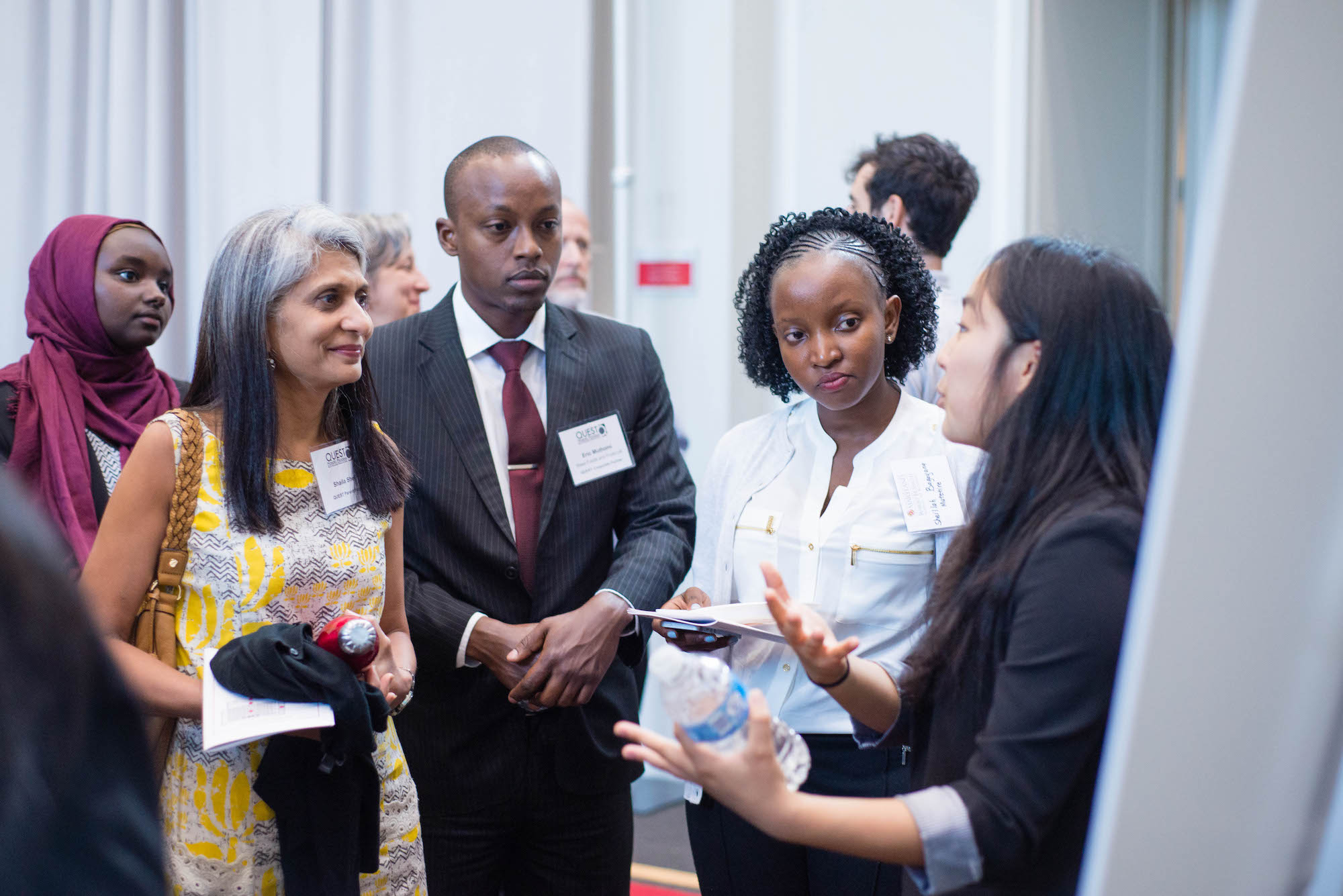 YALI Fellows Eric Muthomi and Sheillah Mutetire (both center) engaged with university faculty and students during the QUEST reception.