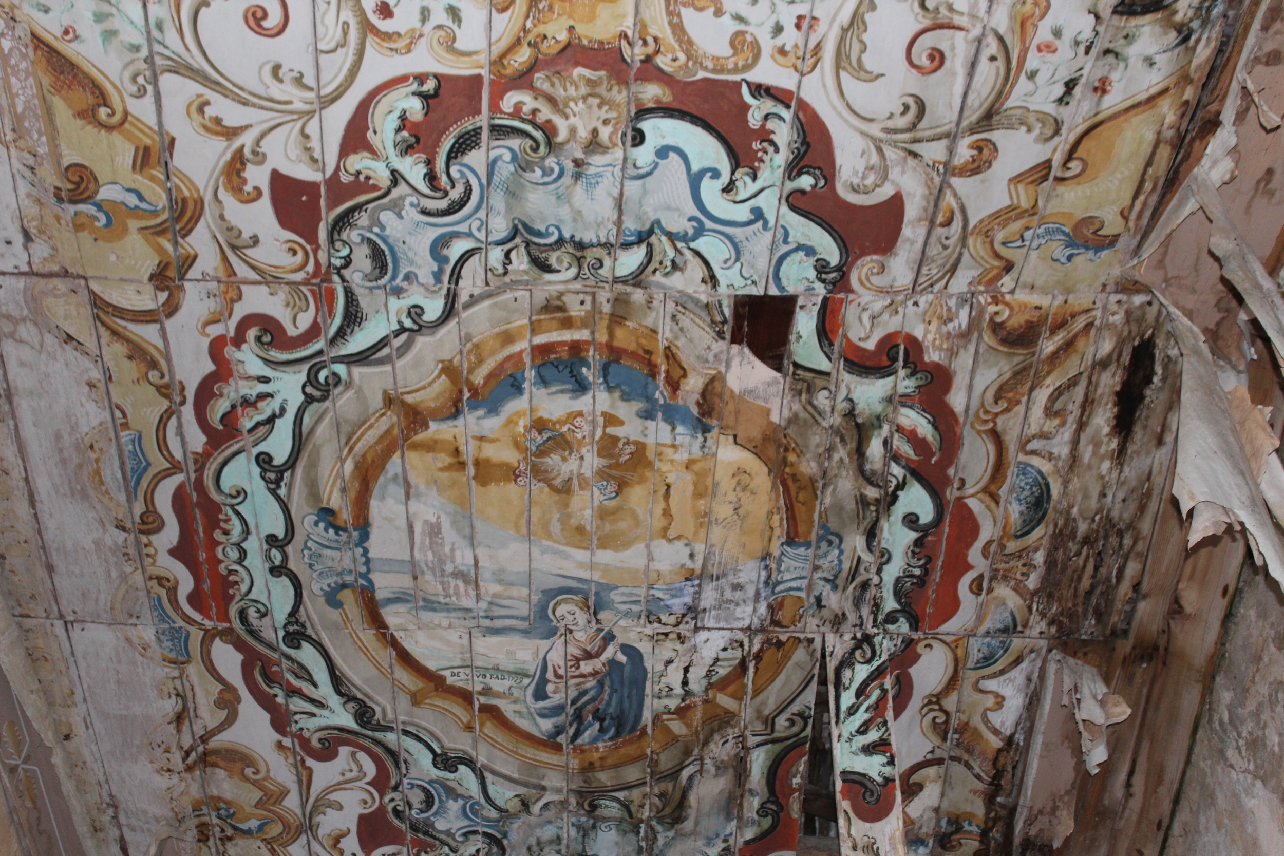 The rotting, painted ceiling of an abandoned chapel in Borgo Castellabate