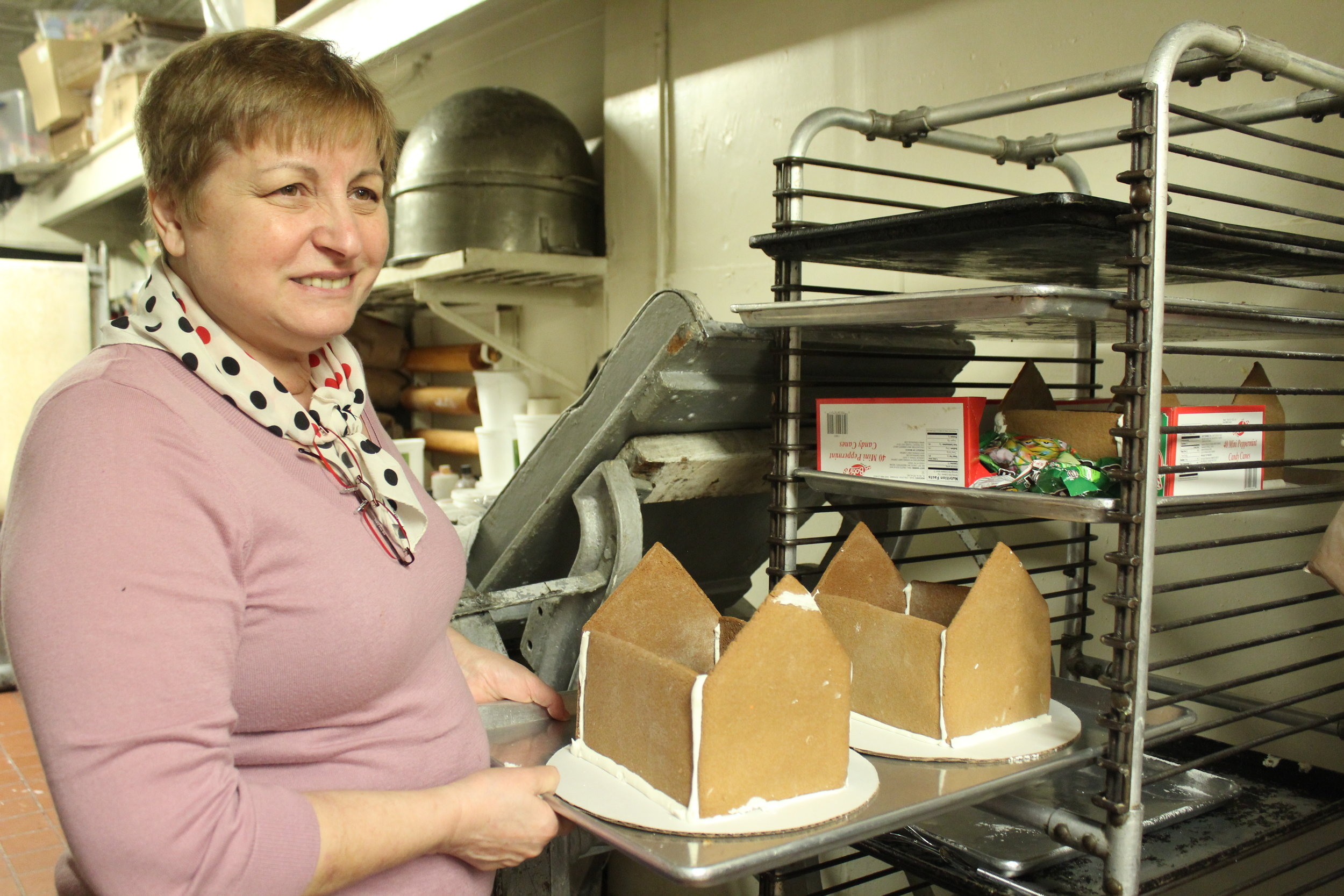 Carmela Lucciola showing off her gingerbread house construction in the kitchen of Egidio's