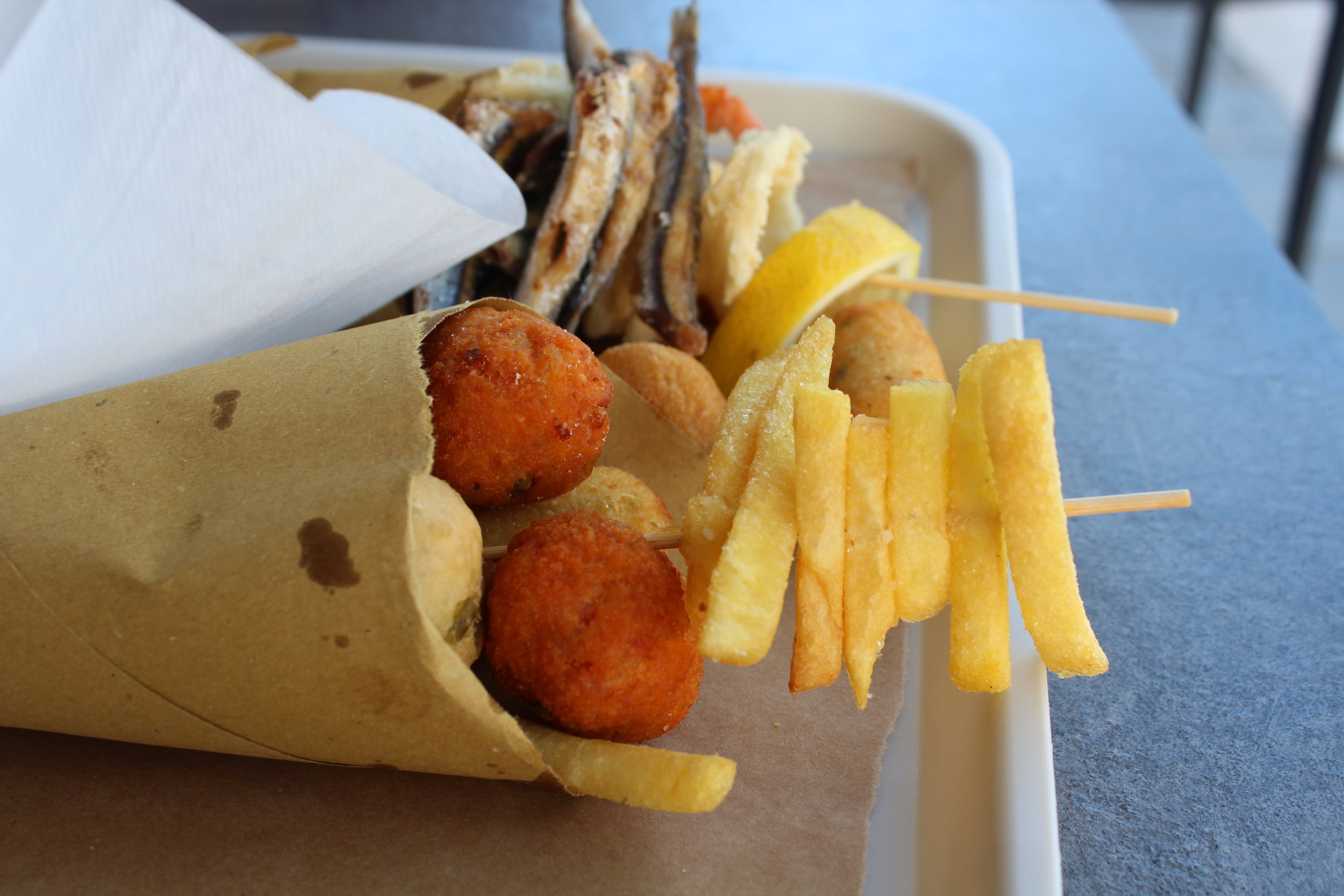 Paper cones of fried fish, pizza dough and fries are available on the beach for just a few Euro