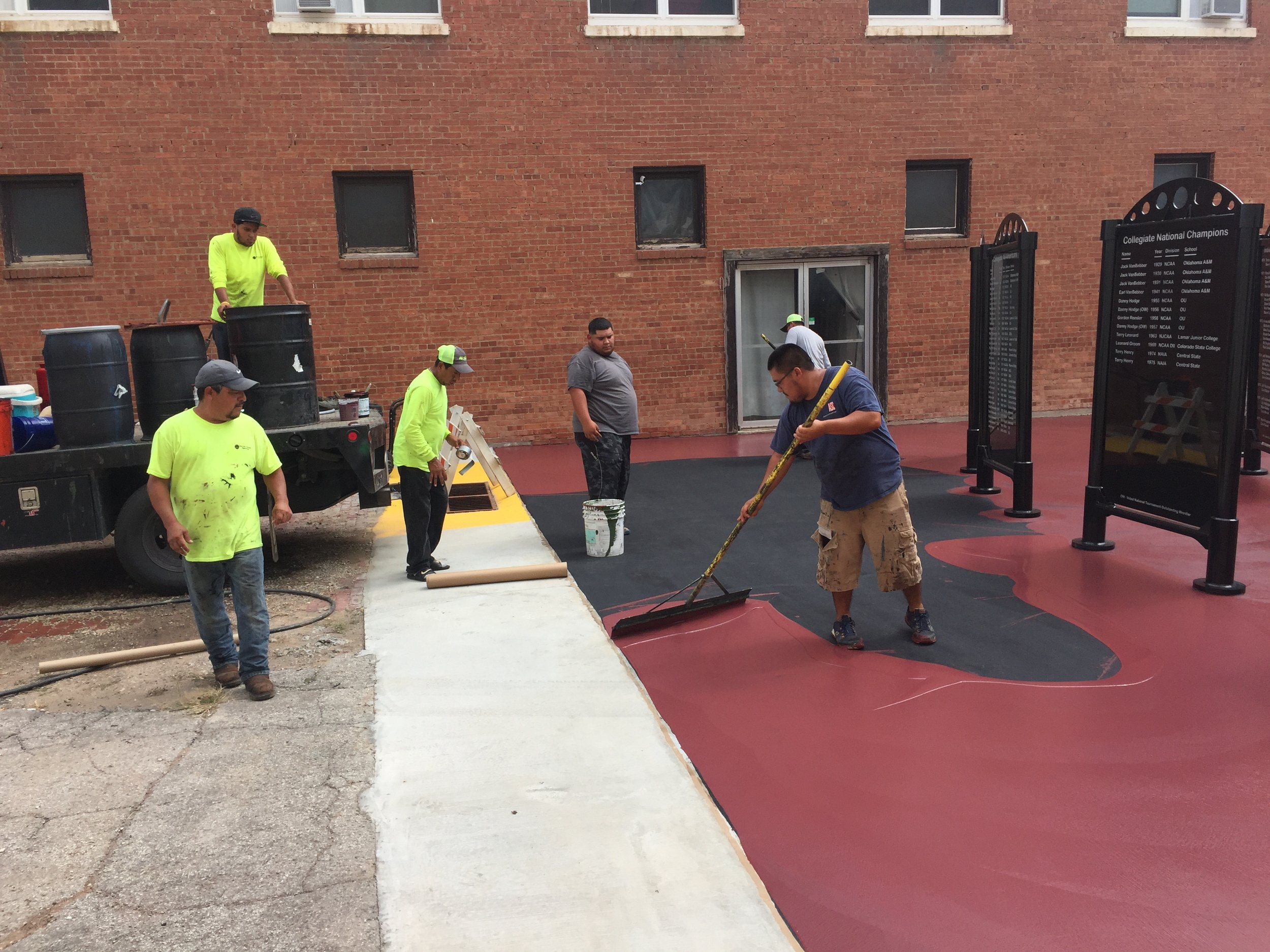 Applying maroon paint on the concrete.   (This is the same type of paint used on tennis courts)