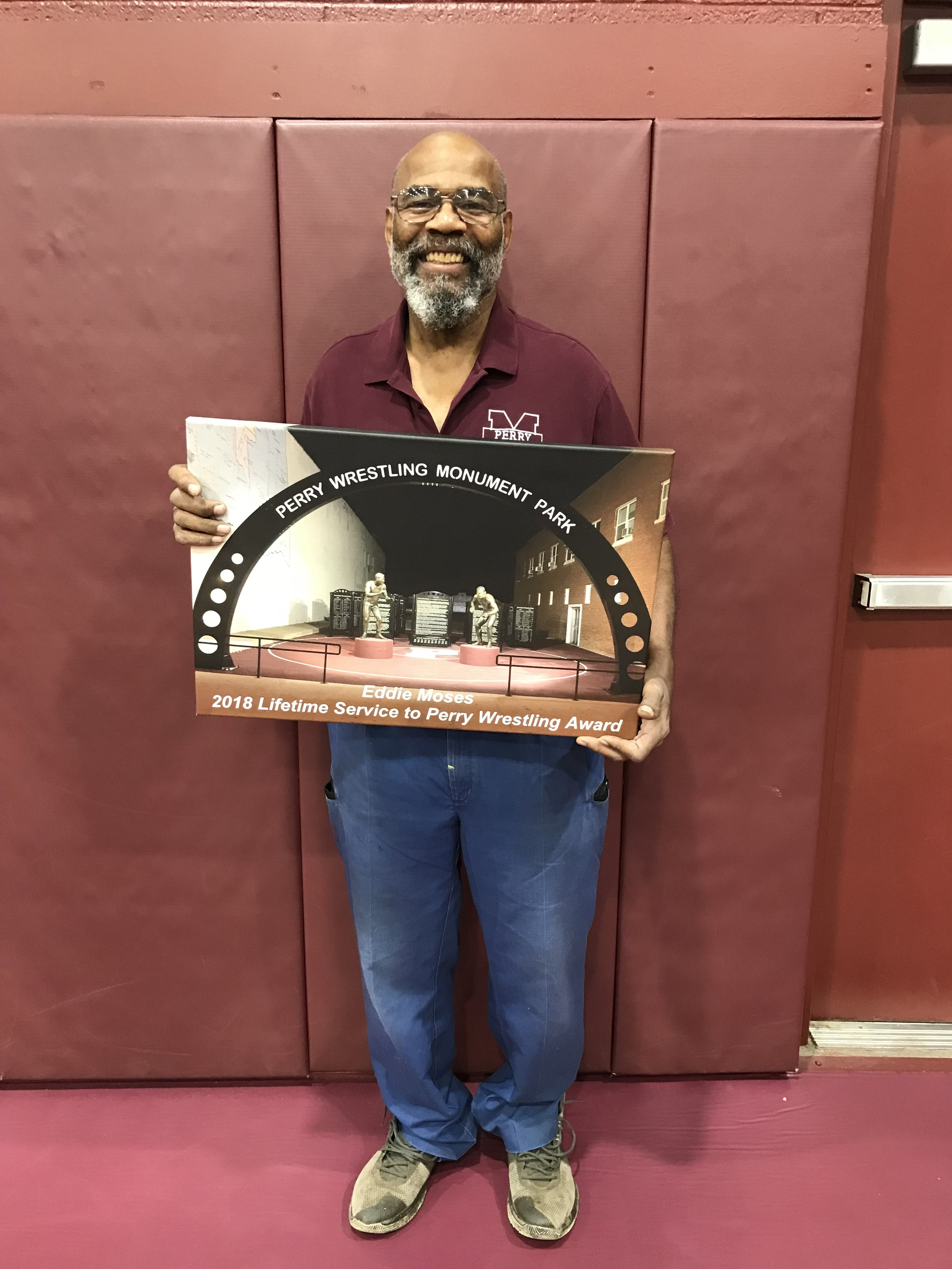 """Eddie Moses   Eddie Moses was a 1975 state runner-up while competing for the Maroons before turning to coaching. He served as a youth coach for many years and was the type of coach that always got the most out of the wrestlers with his positive and uplifting coaching style. His coaching helped develop many young wrestlers that later became high school state champions. For the past several years, his fanatical and enthusiastic support of anything to do with Perry Schools has not gone unnoticed. While a huge supporter of all of the sports, his passion for Perry Wrestling is 2nd to none. He always has a big grin on his face and a """"Can Do"""" attitude that puts everyone around him in a good mood."""