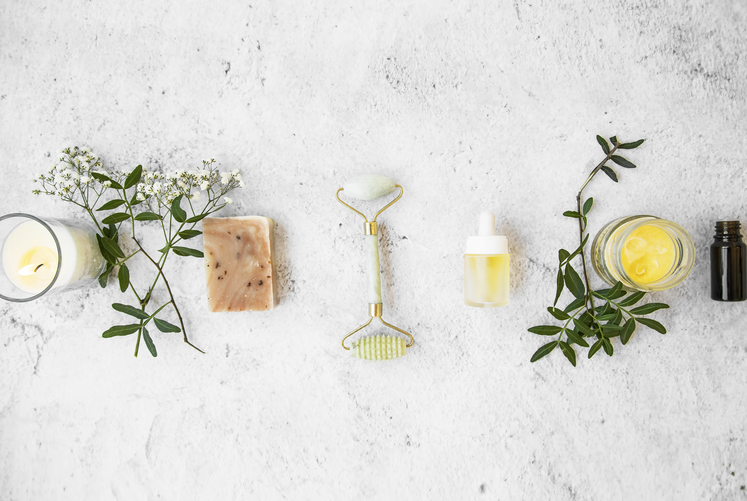 Natural organic skincare products on concrete background, top view, green natural skincare and beauty care with natural soap,jade roller, essential oils bottles, floral extracts and candle