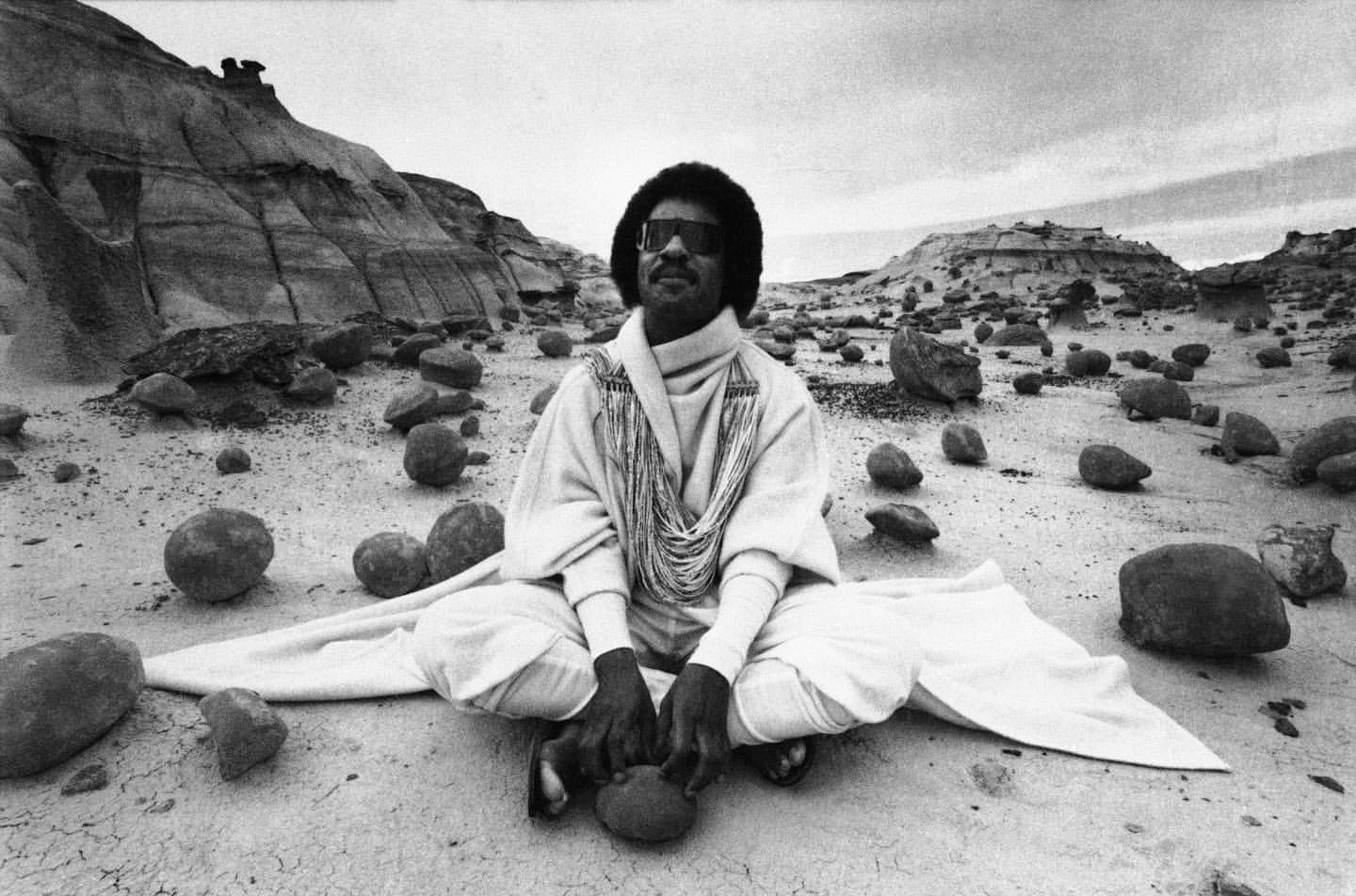 Musician Stevie Wonder sits amid the eerie rocks of the Bisti Badlands in Farmington, New Mexico, filming a commercial, 1982.