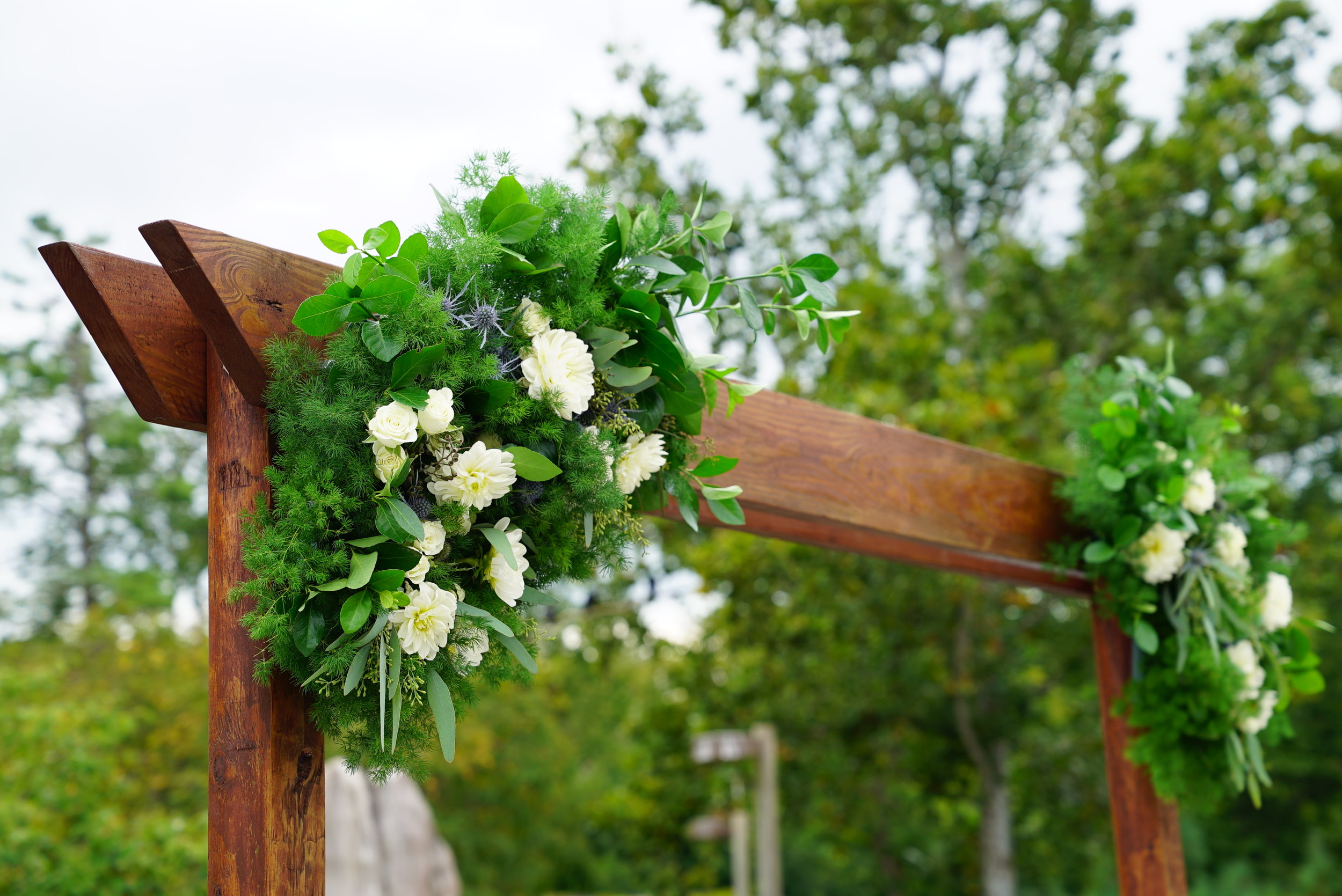 The arch was built using landscaping beams, then stained to match the wood on location. We sunk the uprights into concrete (poured into decorative pots) since the ceremony was on a wooden deck and we had no other way of anchoring the arch into the ground.