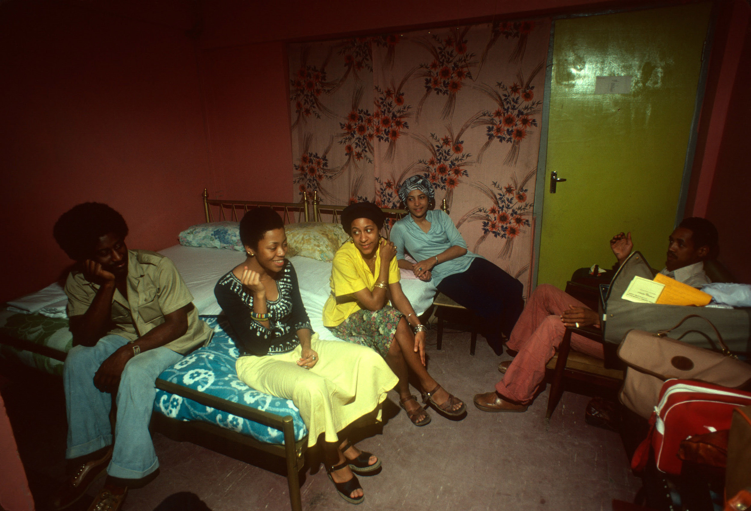 """The Hilltop staff on bed (l. to r., Vance Hawthorne, Vikki Freeman and other Howard students) and old friend, Howard alumnus and our host in Lagos, """"Cincinnati"""" sitting in chair/Calvin Reid"""