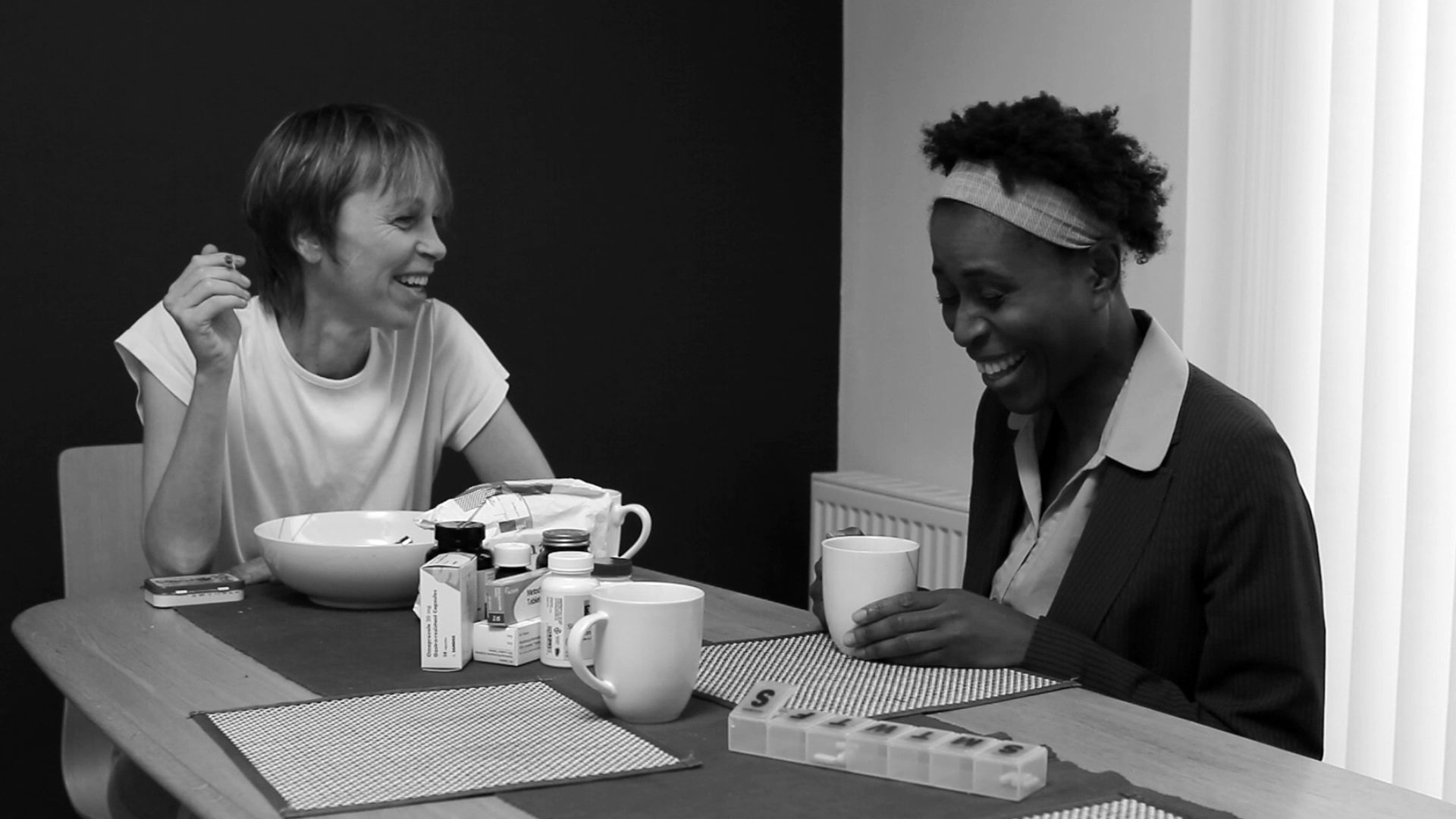 Awake still: two women, one white and one black, laugh over coffee. The white woman holds a joint in her hand.