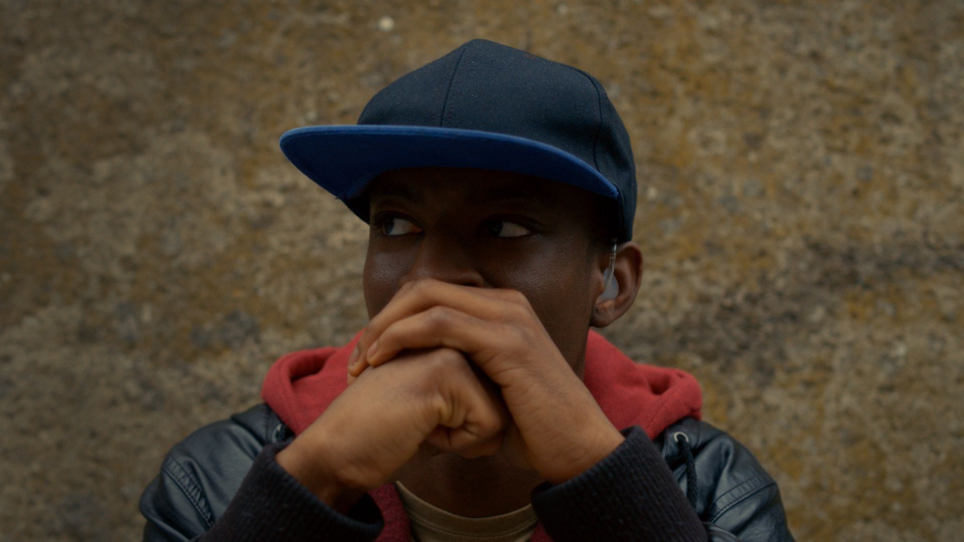 Isaac, a young black man wears a baseball hat and thinks with his hands folded together near his mouth. His hearing aid can be seen.
