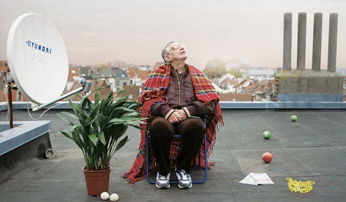 A man sits on a rooftop with a blanket ontop of his shoulders.