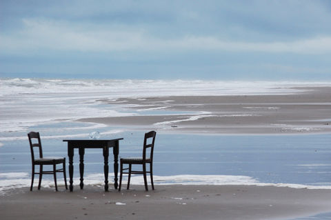 Too chairs and a table sit unoccupied on the beach.