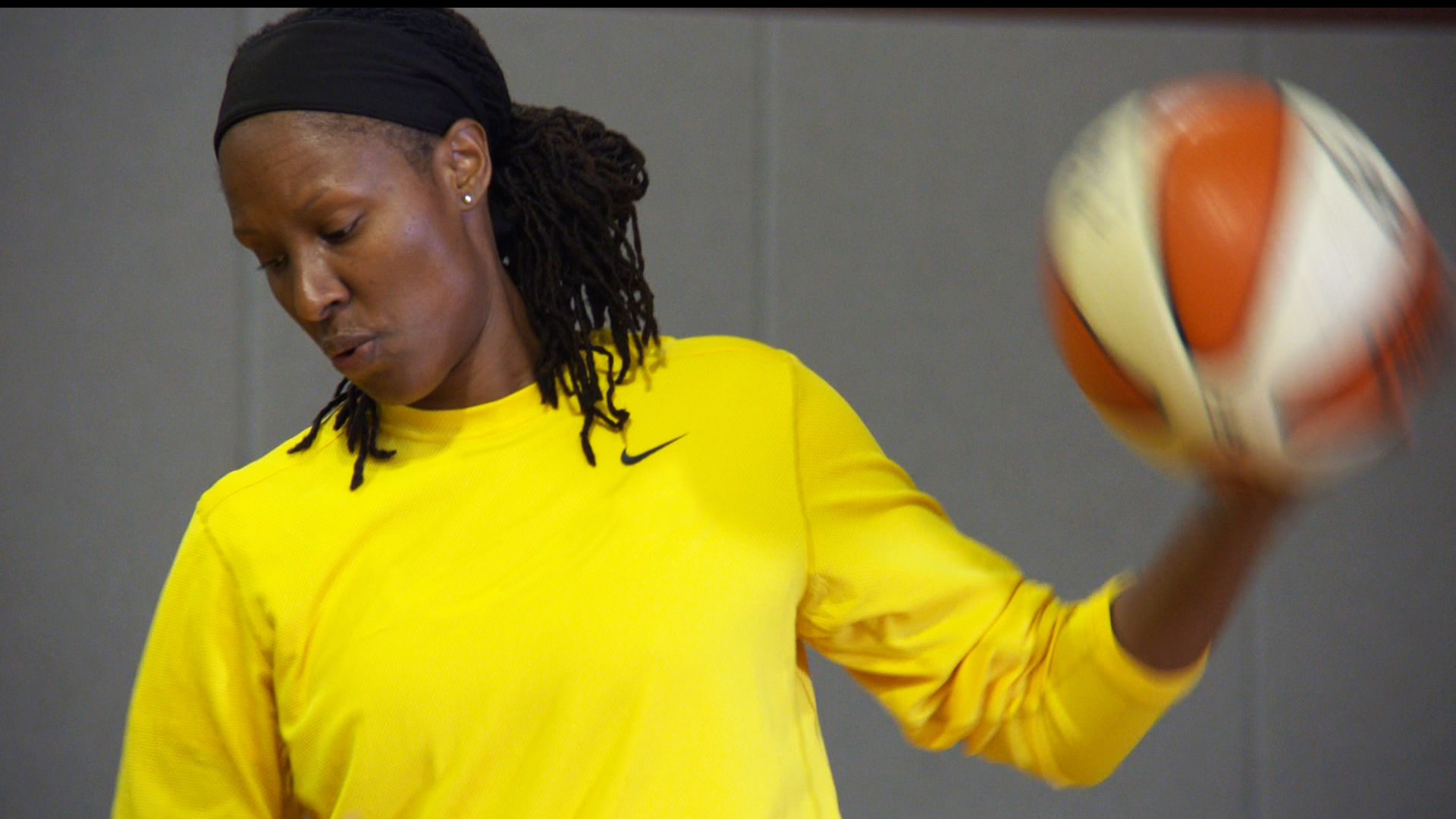 Chamique Holdsclaw, a young athletic black woman, dribbles a basketball