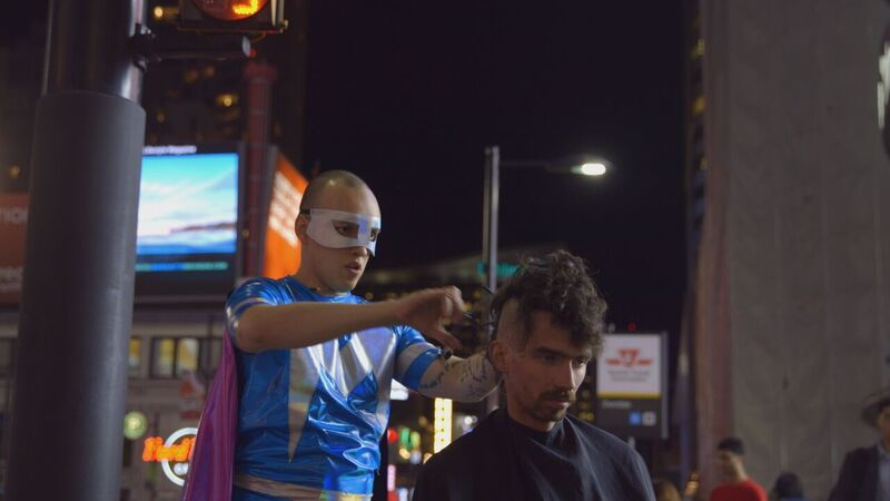 Matthew, in a superhero costume with a cape and mask, cuts a young man's hair in the middle of a busy sidewalk