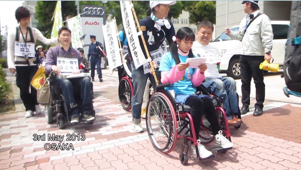 A contingent of wheelchair riding youth march with picket signs down a busy street in Japan