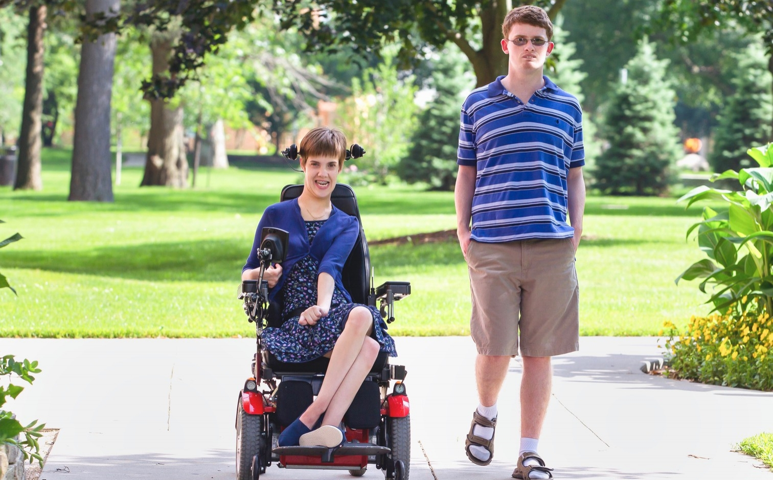 A young woman riding a wheelchair and young man on foot, both white, walk side-by-side in a park