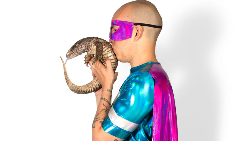 In profile, a man with a shaved head, wearing a shiny superhero costume, kisses the back of a large lizzard