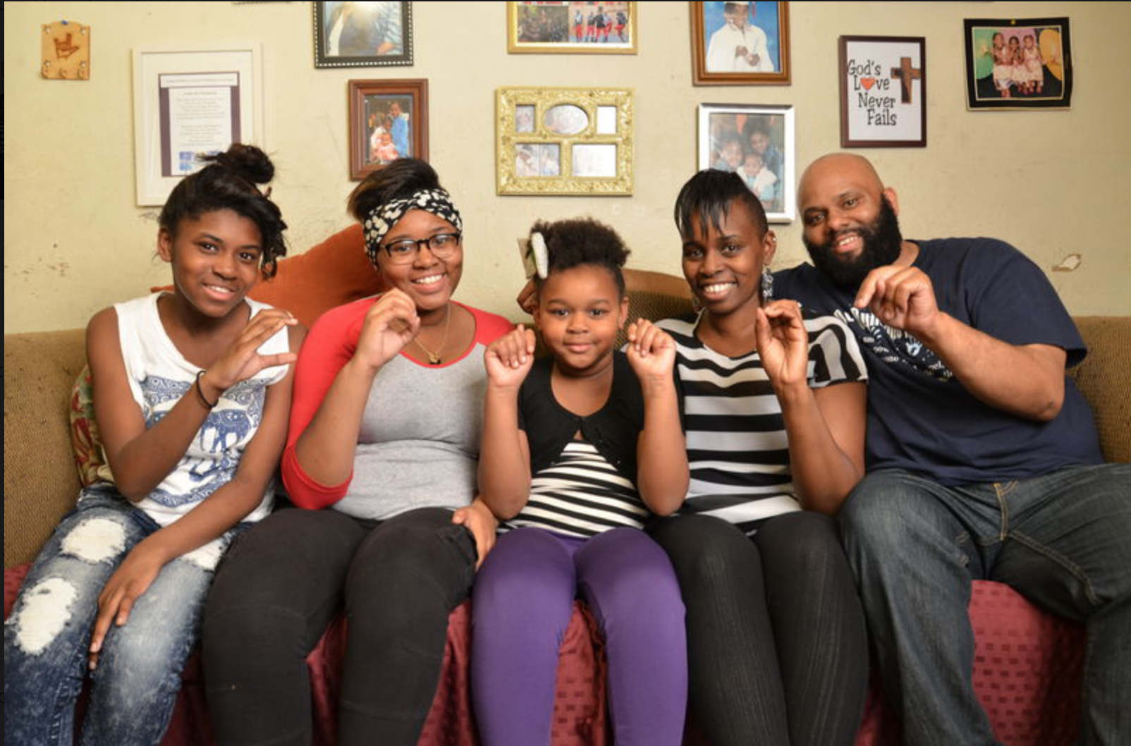 The Cotton family, 3 daughters, mom and dad, sit on their couch and signs their name