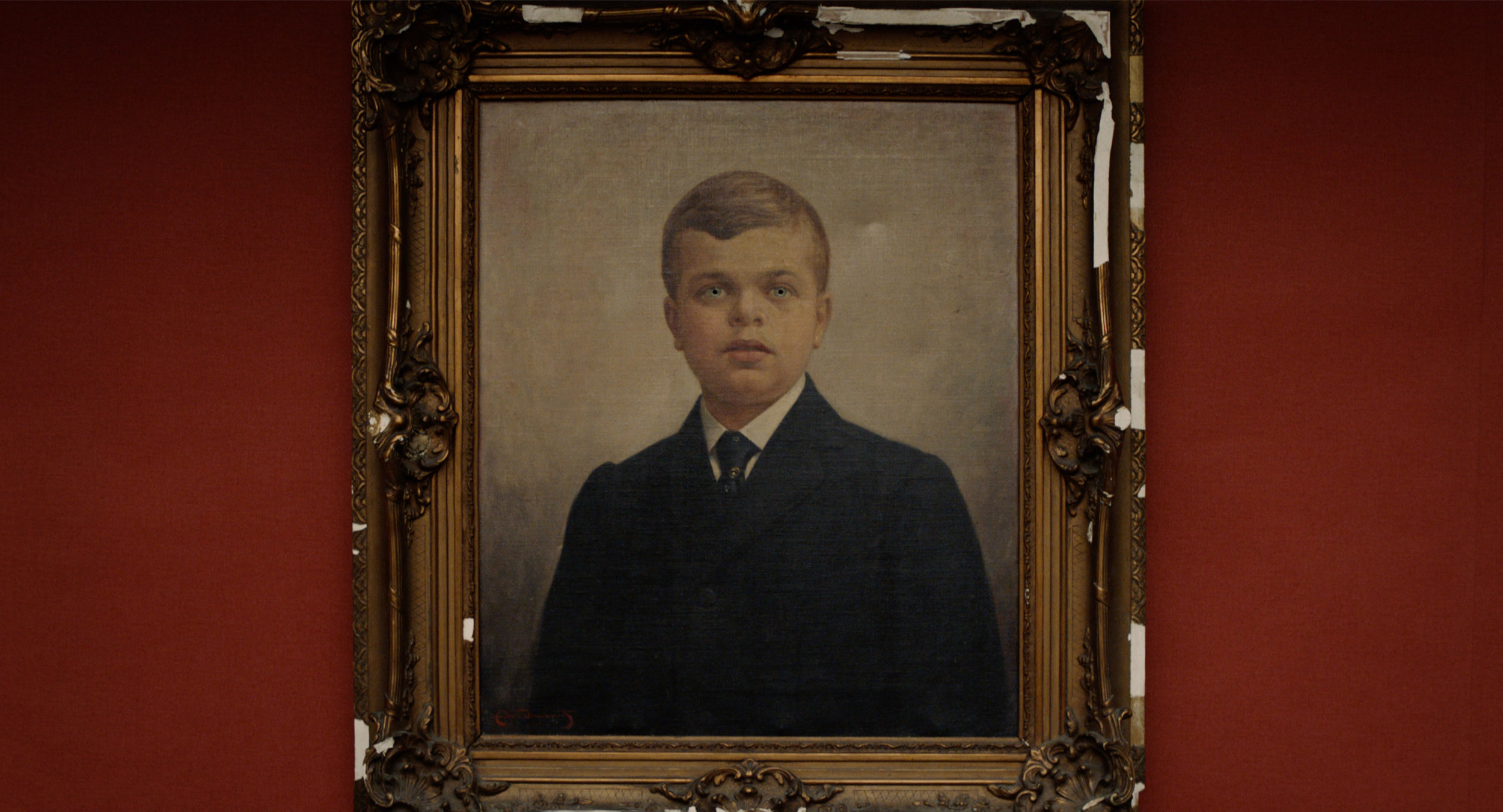 A painted portrait of a young looking man in an intricate frame on a wall of a gallery. He wears a black tuxedo and tie.