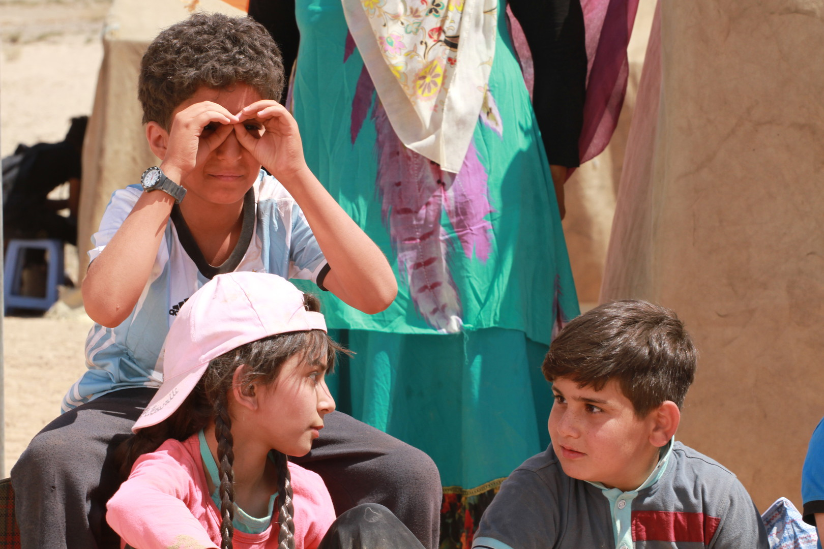 Three children sit in front of an adult whose face is not in the frame. The children's hair and clothes are dusty and wrinkled. Two of the children are looking at each other with concerned faces. The third child holds their hands to their face as if they are looking through binoculars.