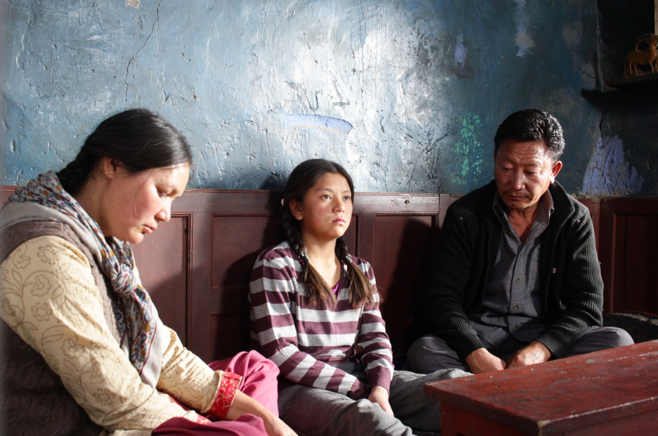 A young girl sits between an older man and woman. The adults are looking down at their laps with hunched shoulders. The young girl looks forward with a pouty mouth.