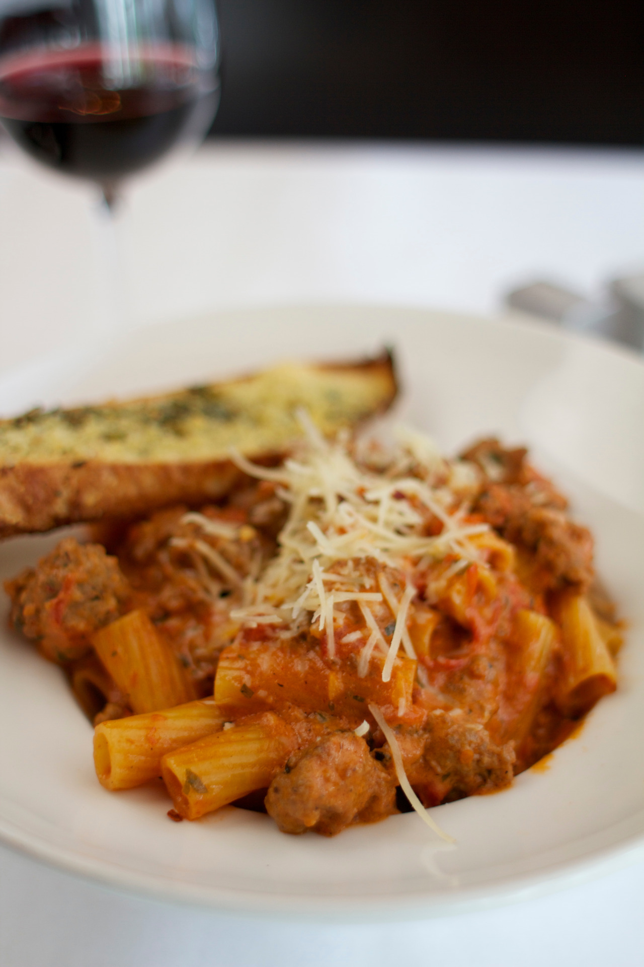 Palomino's  Rigatoni Bolognese (serves 4-6)    1/2lb     Uli's Famous Hot Italian Sausage    1/4tsp   Crushed Red Chili Pepper Flakes   1lb      Crushed Pair Tomatoes in Juice   2tbsp    Minced Parsley   2tbsp    Minced Garlic   1/4cup   Roasted Red Peppers (julienned)   2tsp     Dried Oregano   1cup    Heavy Cream   1 1/4lb   Rigatoni (cooked)   Salt and Pepper to taste   1. Brown  Uli's Famous Hot Italian Sausage  in a large pan over medium heat. Add tomatoes, garlic, chili pepper, red peppers, parsley, and oregano. Simmer uncovered for 20 minutes until slightly thickened.   2. Add heavy and bring to a simmer. Add cooked pasta and simmer to coat the noodles. Top with grated parmesan and minced parsley.   3. Enjoy with your friends and family. For those who need to do a little less spice try  Uli's Famous Mild Italian Sausage .